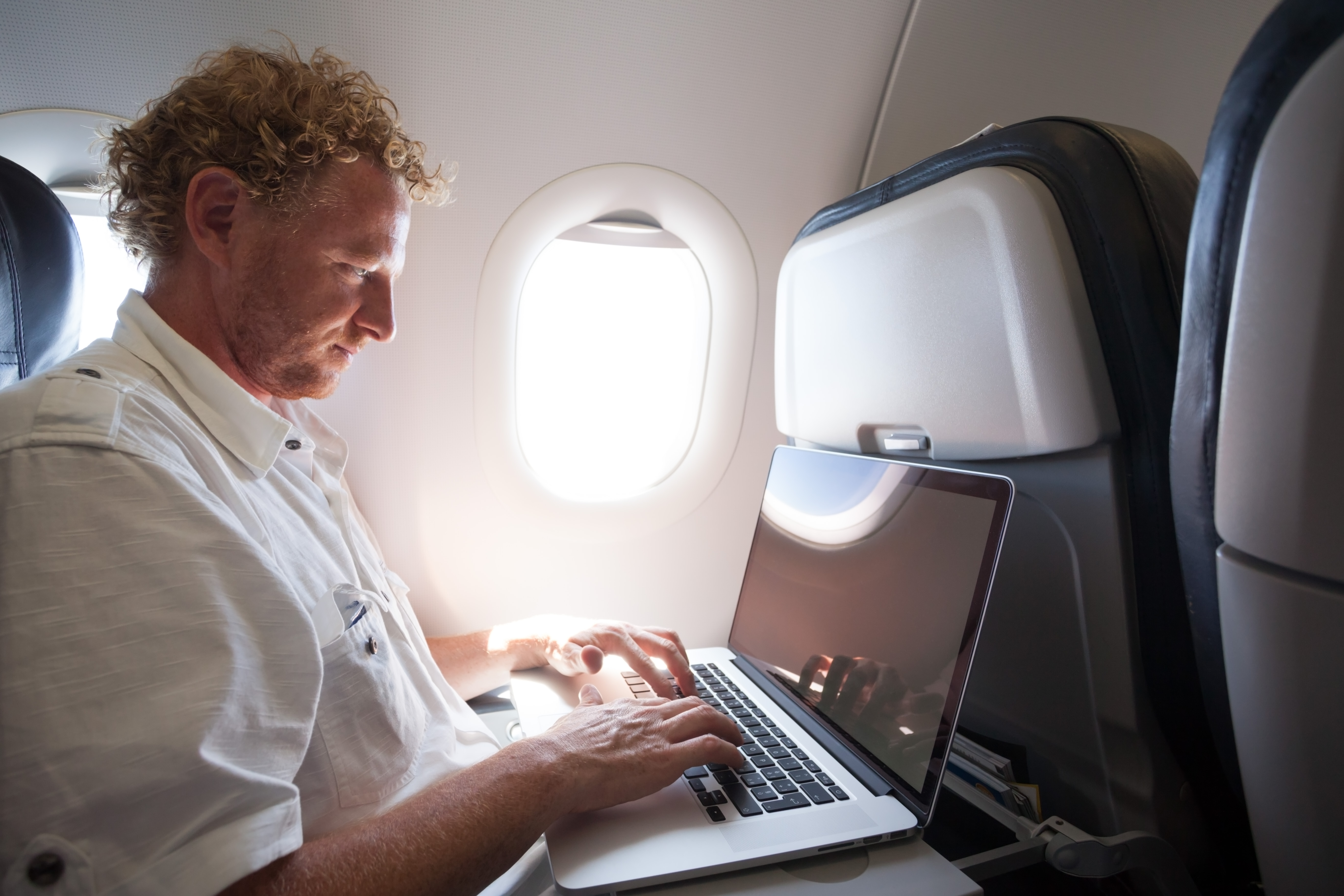 Adult man using laptop on the plane