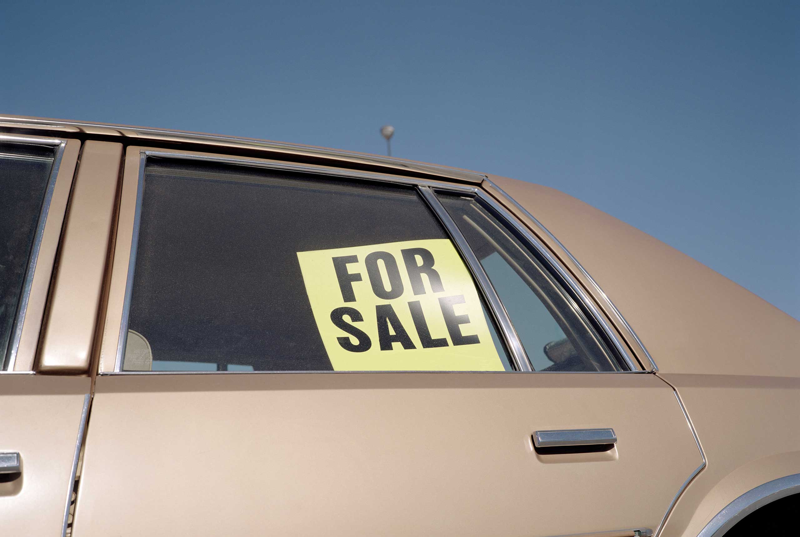 'For Sale' sign placed in car window, outdoors, close-up