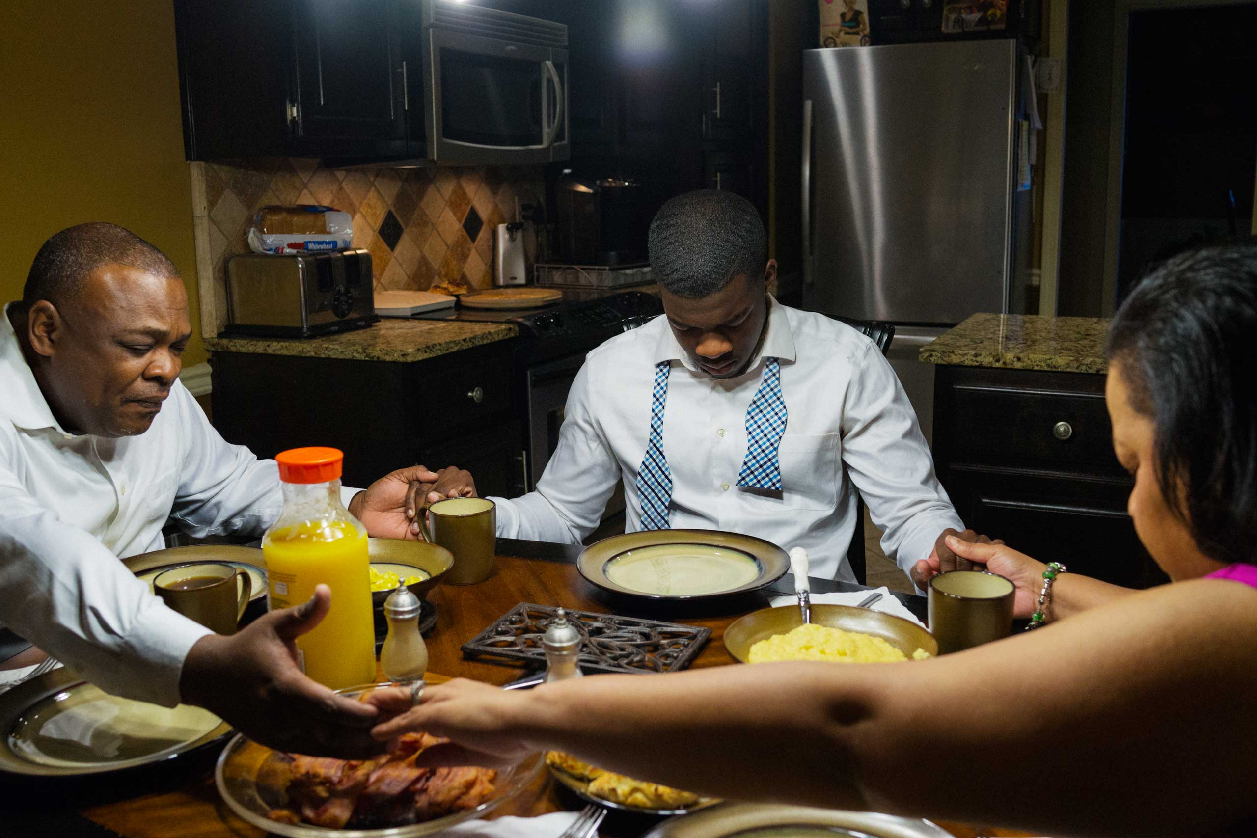 "Pietro ""P.J."" Garrett, 17, and his family pray at breakfast before heading to services at 16th Street Baptist Church."