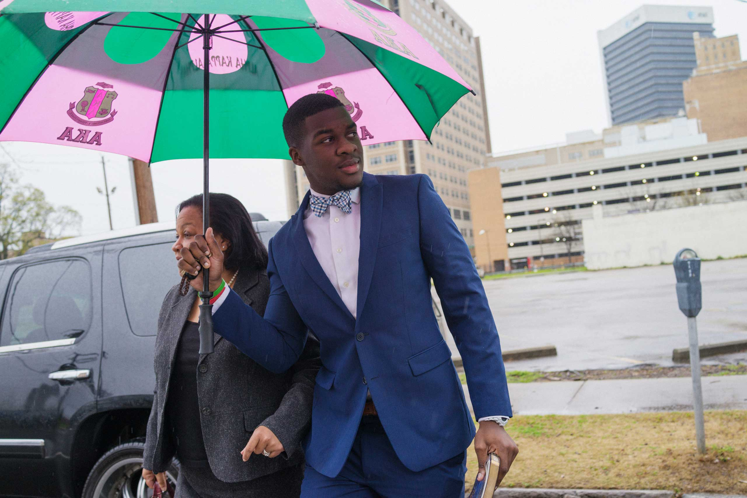P.J. Garrett holds an umbrella for his mother, Dr. Cynthia Garrett, as they arrive at 16th Street Baptist Church.