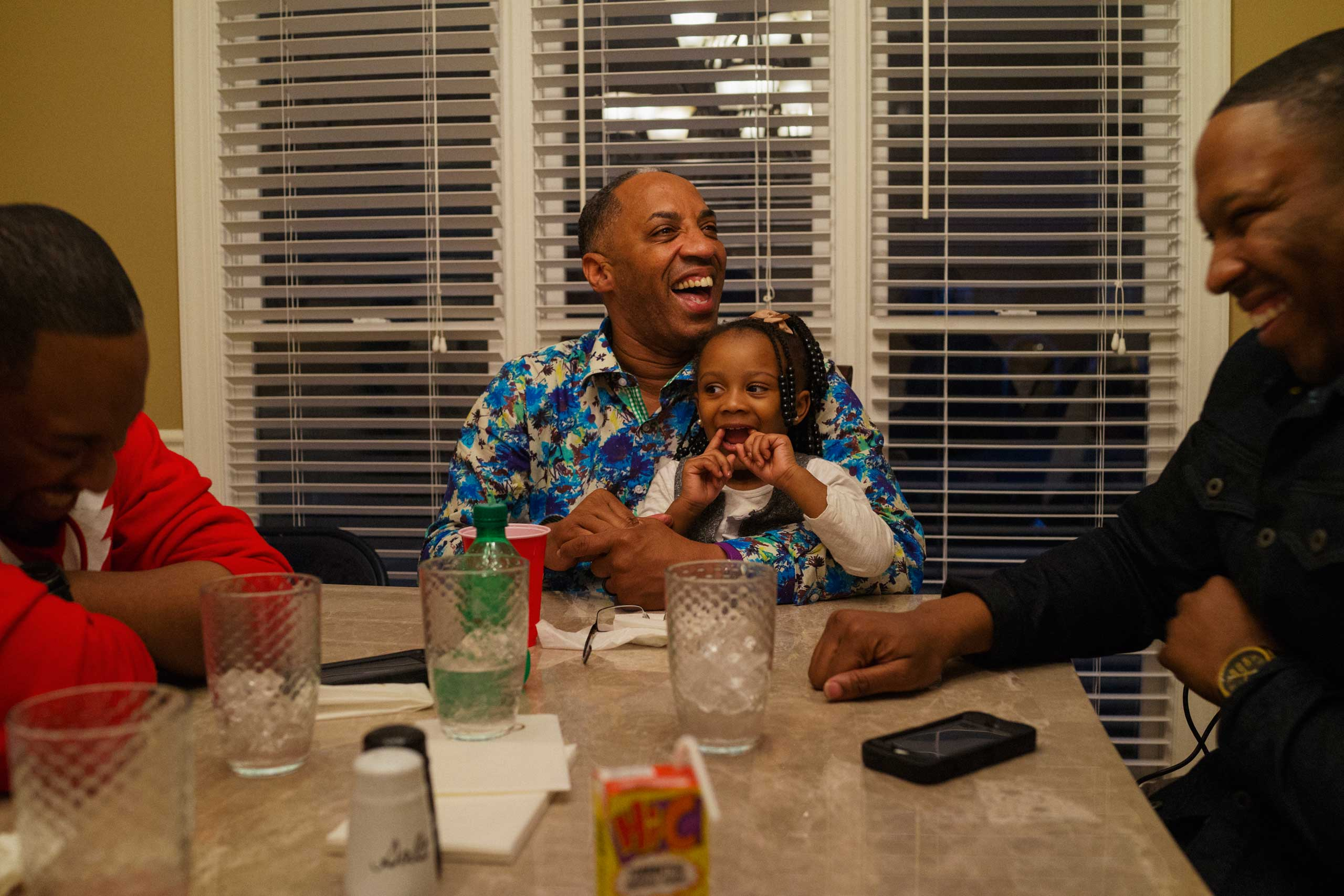 (L-R) Michael McClure Jr., Michael McClure Sr. and his granddaughter Brooklyn, and Darius McClure laugh during a family dinner at the home of Rev. Michael McClure Sr., in Birmingham, Ala. on March 22, 2015.