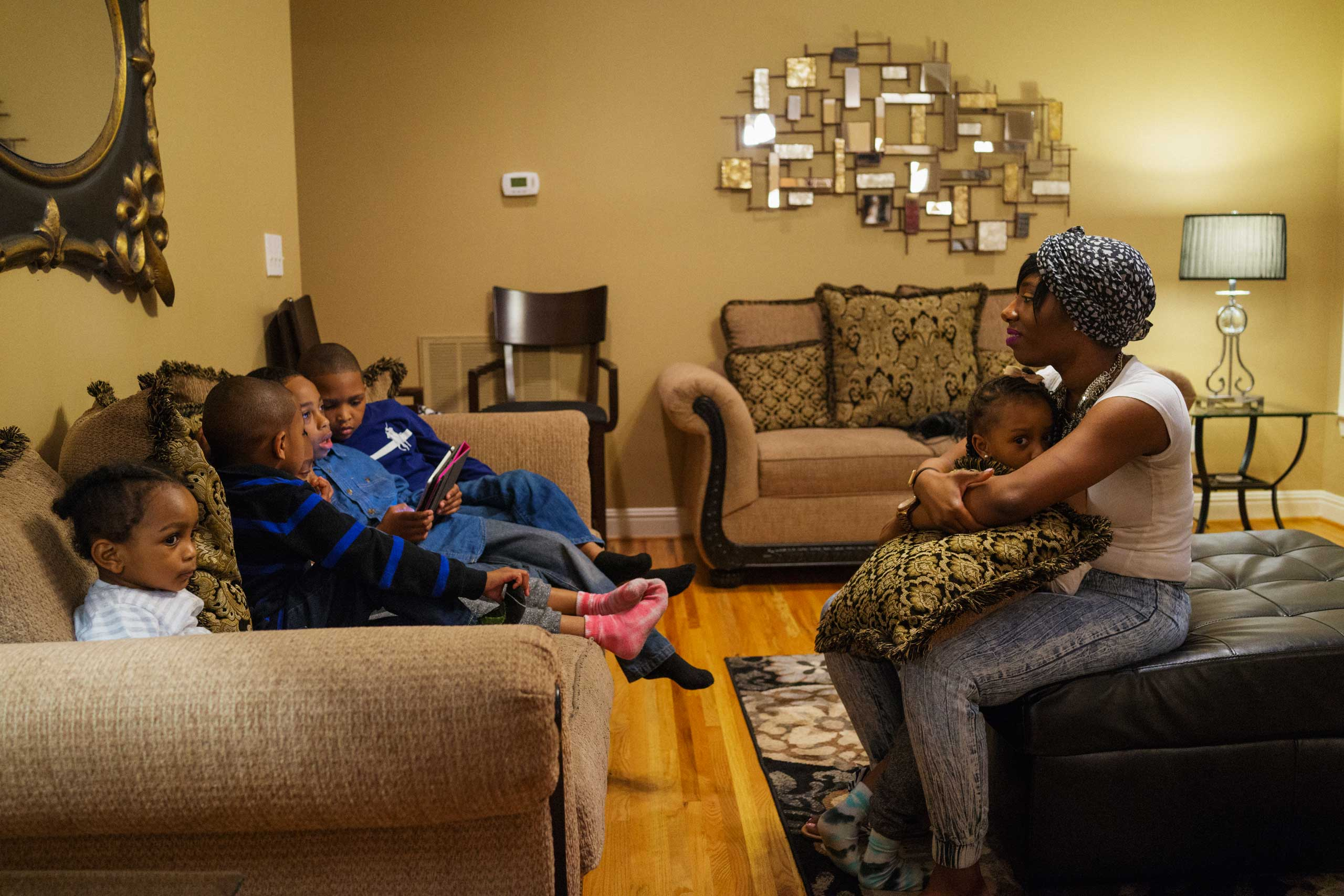 Angelique McClure hangs out with her nieces and nephews in the living room during a family dinner at her father's home.