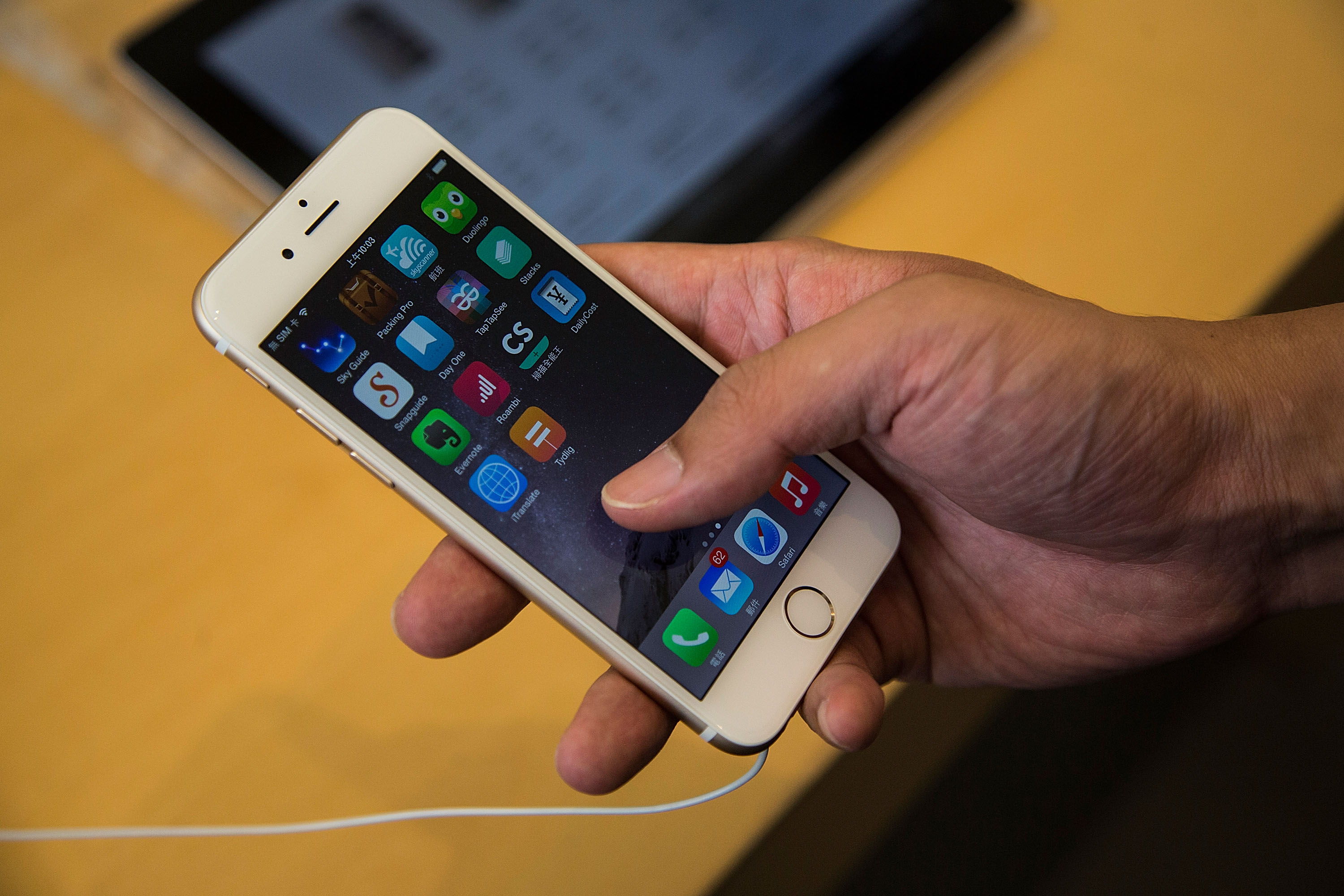 Customer looks at the new iPhones on display at the launch of the new Apple iPhone 6 and iPhone 6 Plus at the Apple IFC store on September 19, 2014 in Hong Kong, China.