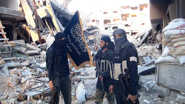 Fighters from the al-Qaida group in the Levant, Al-Nusra Front,  stand among destroyed buildings near the front line with Syrian government solders in  Yarmuk Palestinian refugee camp, south of Damascus on September 22, 2014. The Syrian Observatory for Human Rights says more than 180,000 people have been killed in the Syrian conflict since it erupted in March 2011, while the United Nations puts the figure at 191,000. AFP PHOTO/ RAMI AL-SAYED        (Photo credit should read RAMI AL-SAYED/AFP/Getty Images)