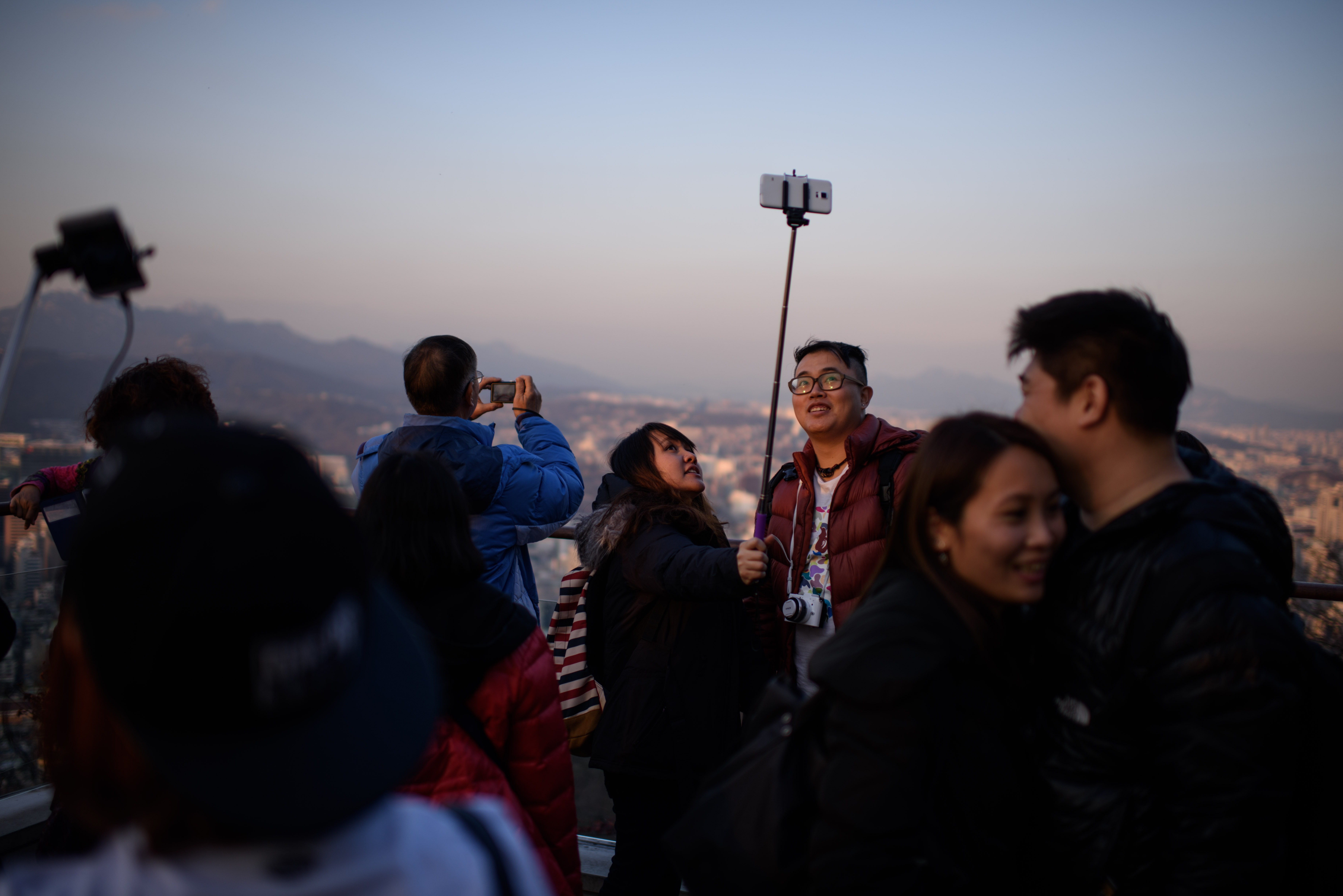 People use a 'selfie stick' to take a group photo overlooking the city skyline in Seoul, South Korea, on Nov. 26, 2014