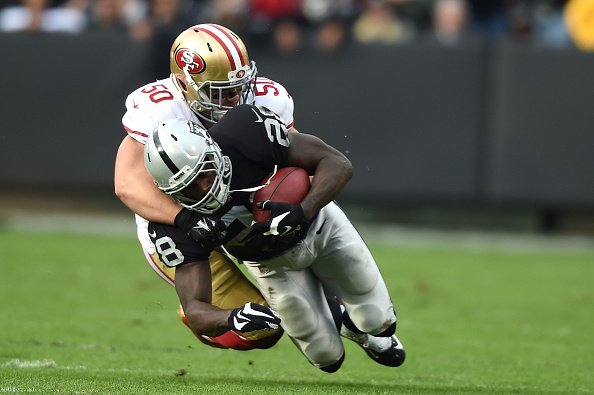 Latavius Murray of the Oakland Raiders is tackled by Chris Borland of the San Francisco 49ers O.co Coliseum in Oakland, Calif., on Dec. 7, 2014