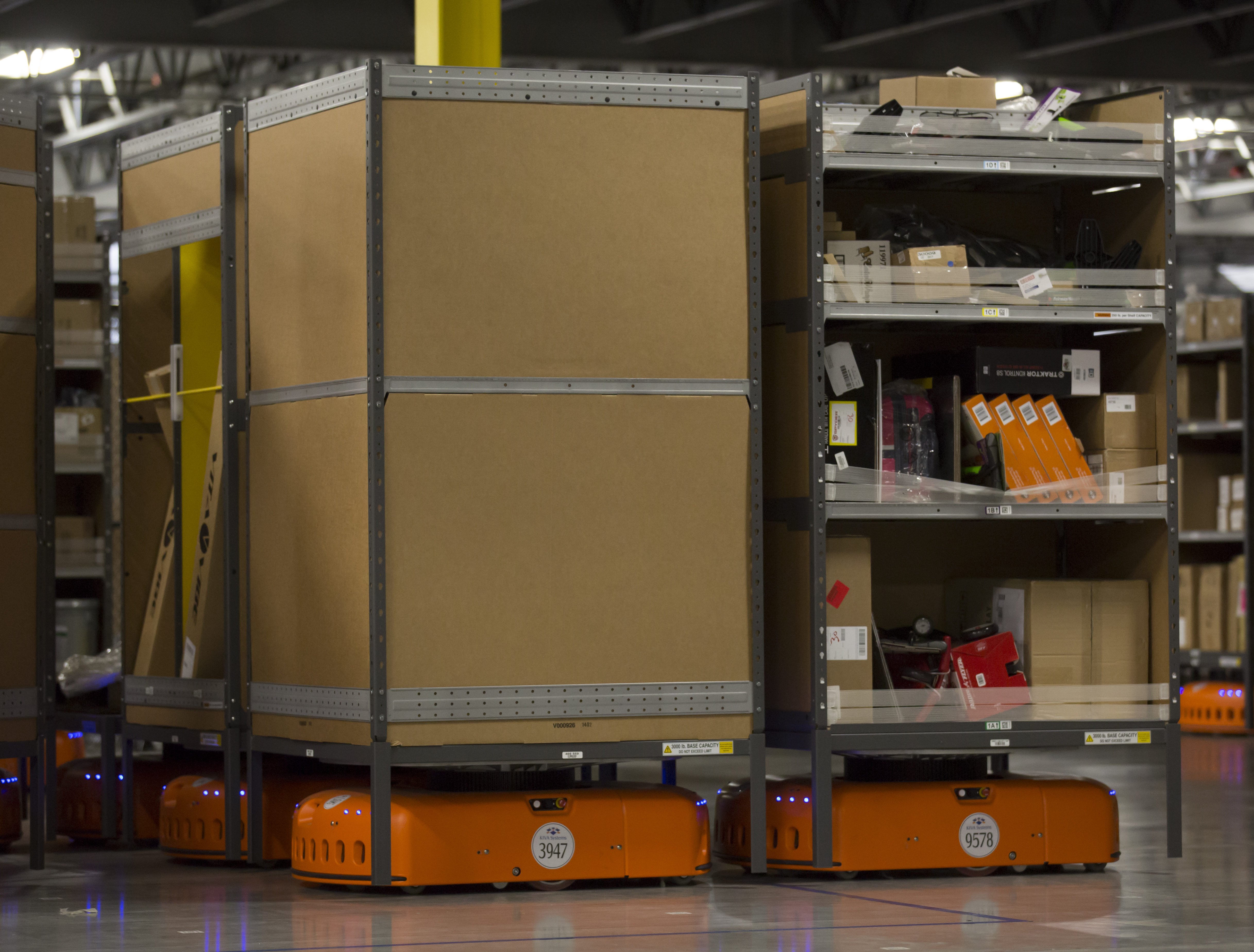 Amazon Kiva robots, which help fill orders by bringing shelves of merchandise to Amazon Associates, navigate an Amazon Fulfillment Center on February 13, 2015 in DuPont, Washington.