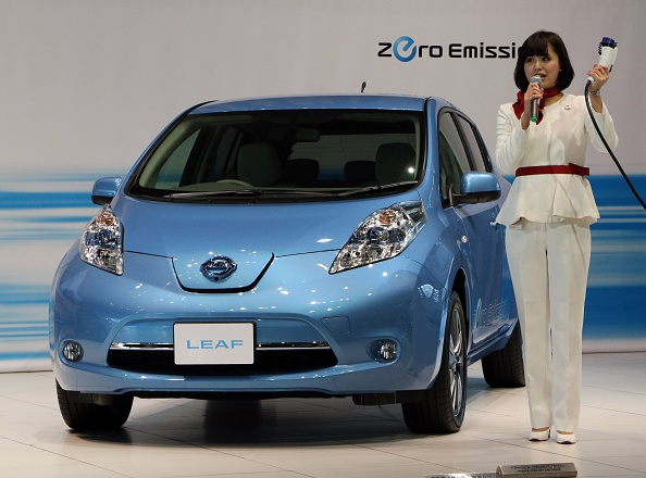 This picture taken on February 9, 2015 shows an employee of Japanese auto giant Nissan Motor demonstrating how to charge the company's electric vehicle Leaf at the company's showroom in Yokohama, suburban Tokyo. Green-car sceptics take note: Japan now has more electric vehicle charging spots than gas stations. The country's number-two automaker Nissan says on February 17 there are now 40,000 charging units -- including those inside private homes -- across the nation, compared with 34,000 petrol stations.   AFP PHOTO / Yoshikazu TSUNO        (Photo credit should read YOSHIKAZU TSUNO/AFP/Getty Images)
