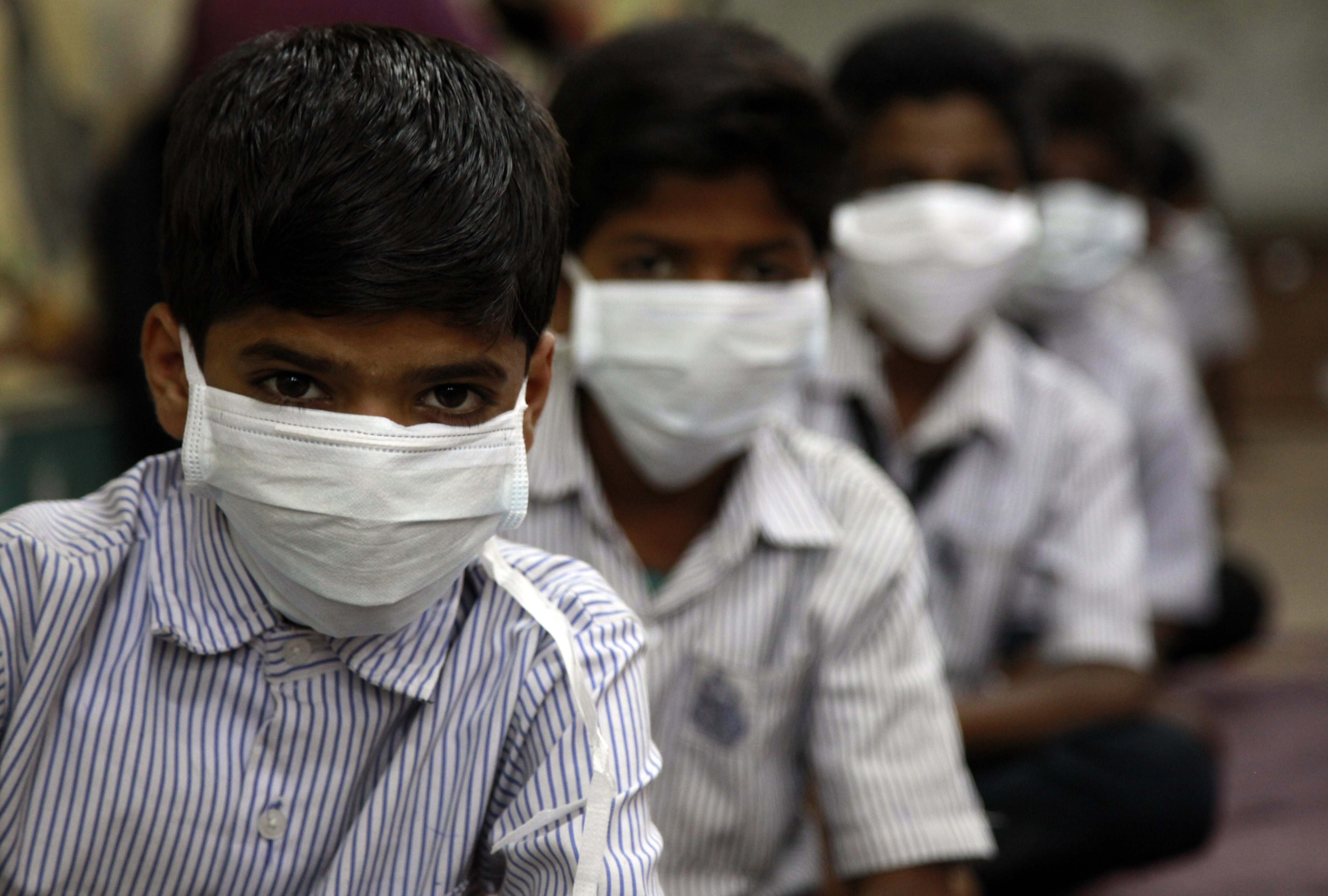 A class of Indian students have taken to wearing masks to avoid contracting swine flu in Mumbai, India on 20 February, 2015.