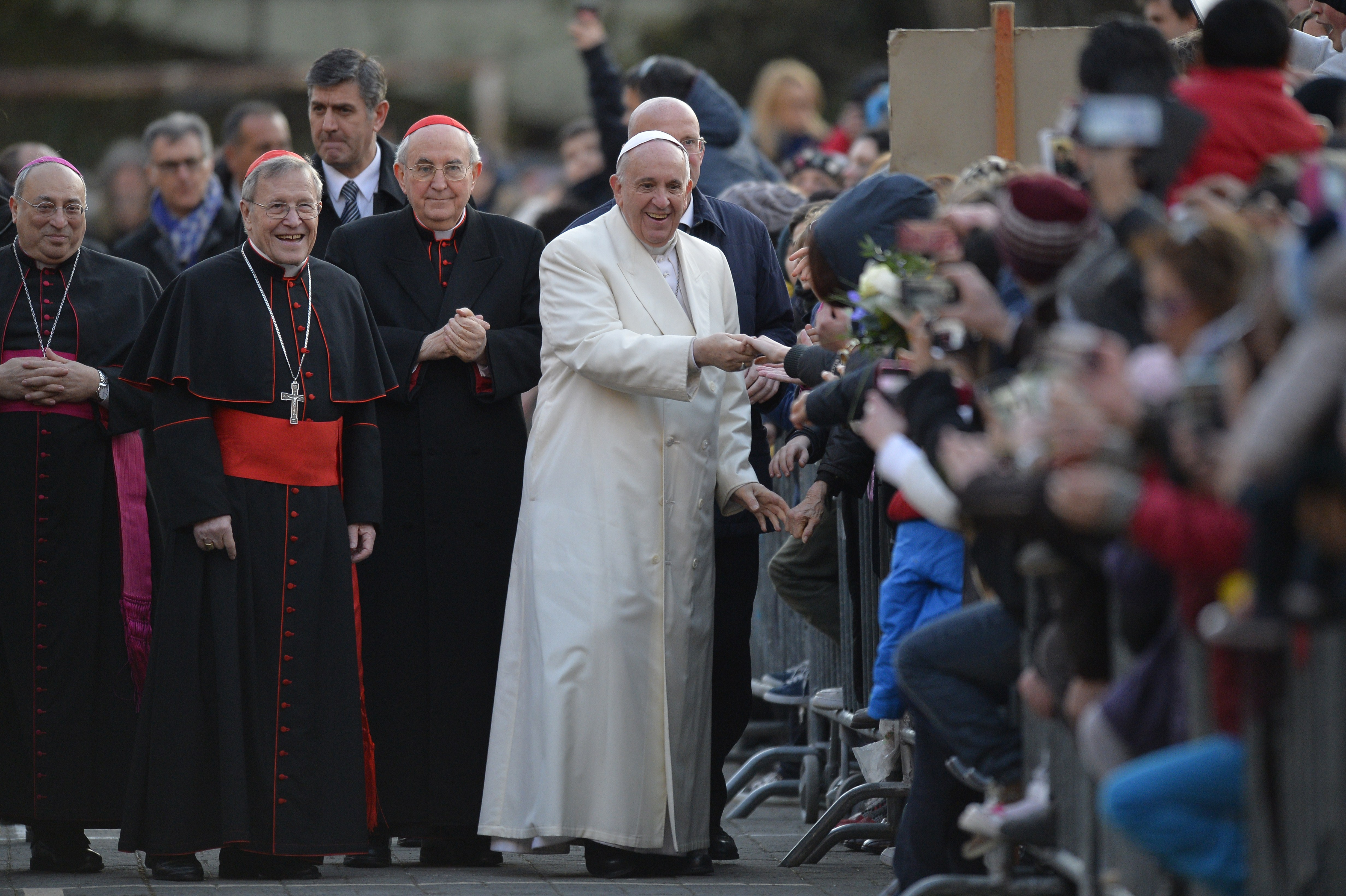 Pope Francis (C) greets the crowd as he arrives for a visit to the Roman Parish of  Ognissanti  on March 7, 2015 in Rome.