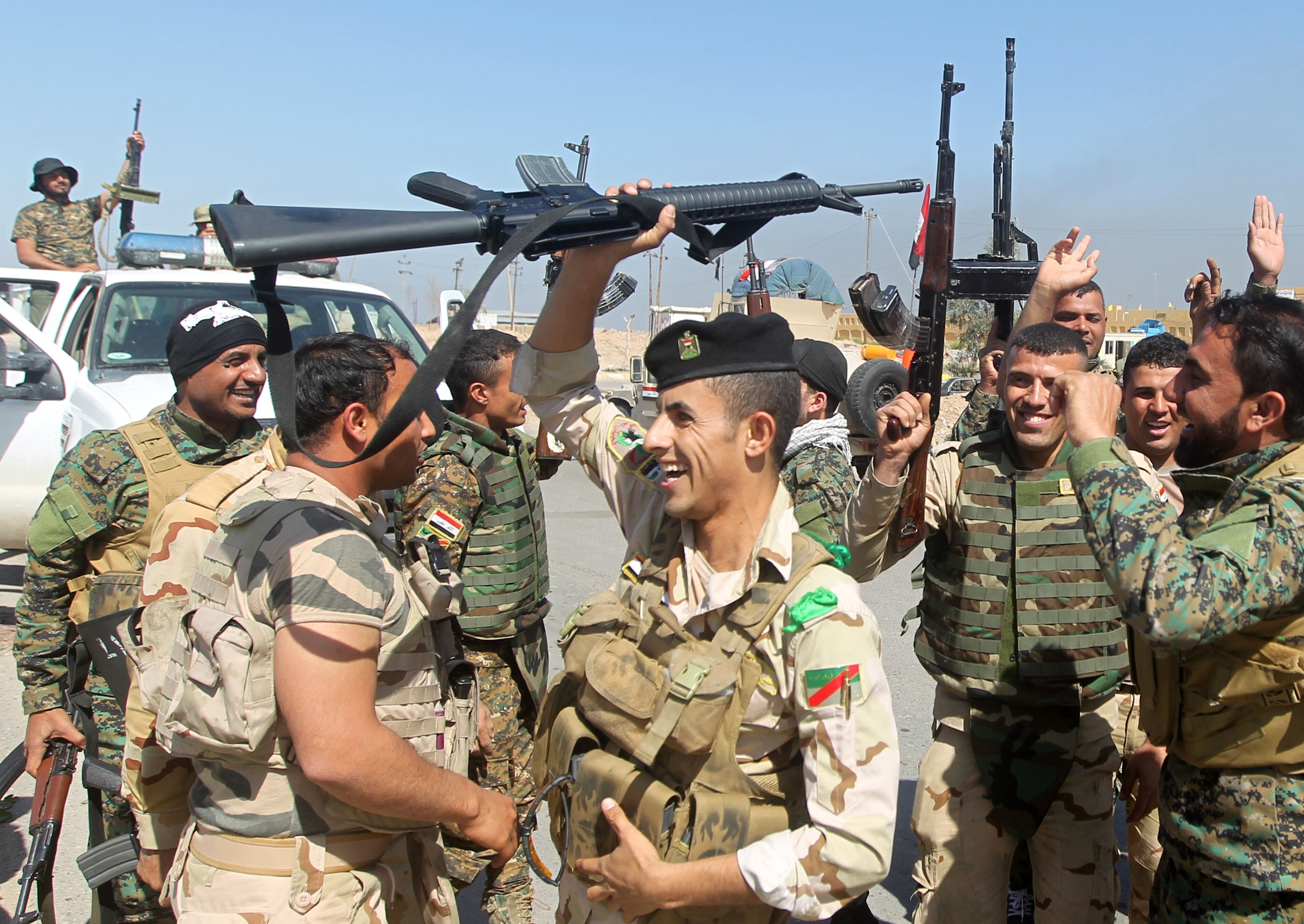Iraqi soldiers raise their weapons as they cheer on the outskirts of the city of Tikrit as they prepare to launch a military operation to take control of the city from ISIS on March 10, 2015.