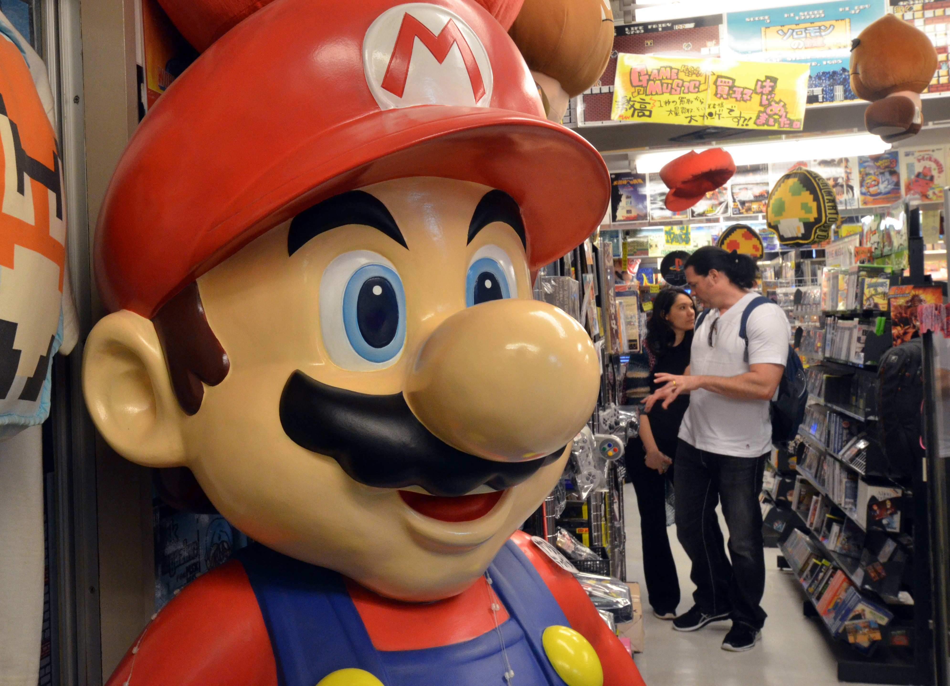 This picture taken on April 17, 2014 shows customers check used videogame consoles and softwares at a videogame shop in Tokyo, while a large figure of Nintendo's character Super Mario stands.