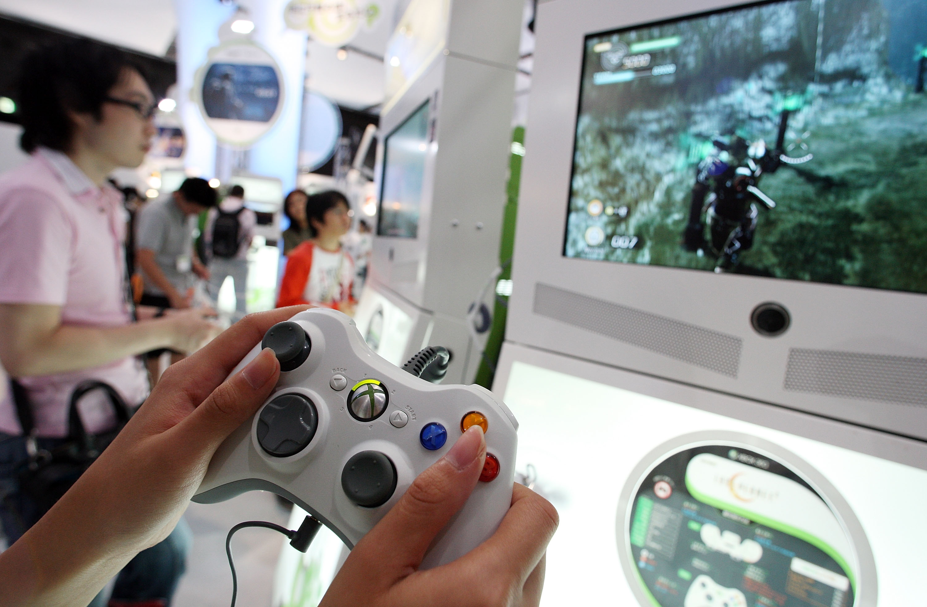 Visitors play with the XBOX 360 at the Microsoft booth during the Tokyo Game Show 2009 press and business day at Makuhari Messe on September 24, 2009 in Chiba, Japan.