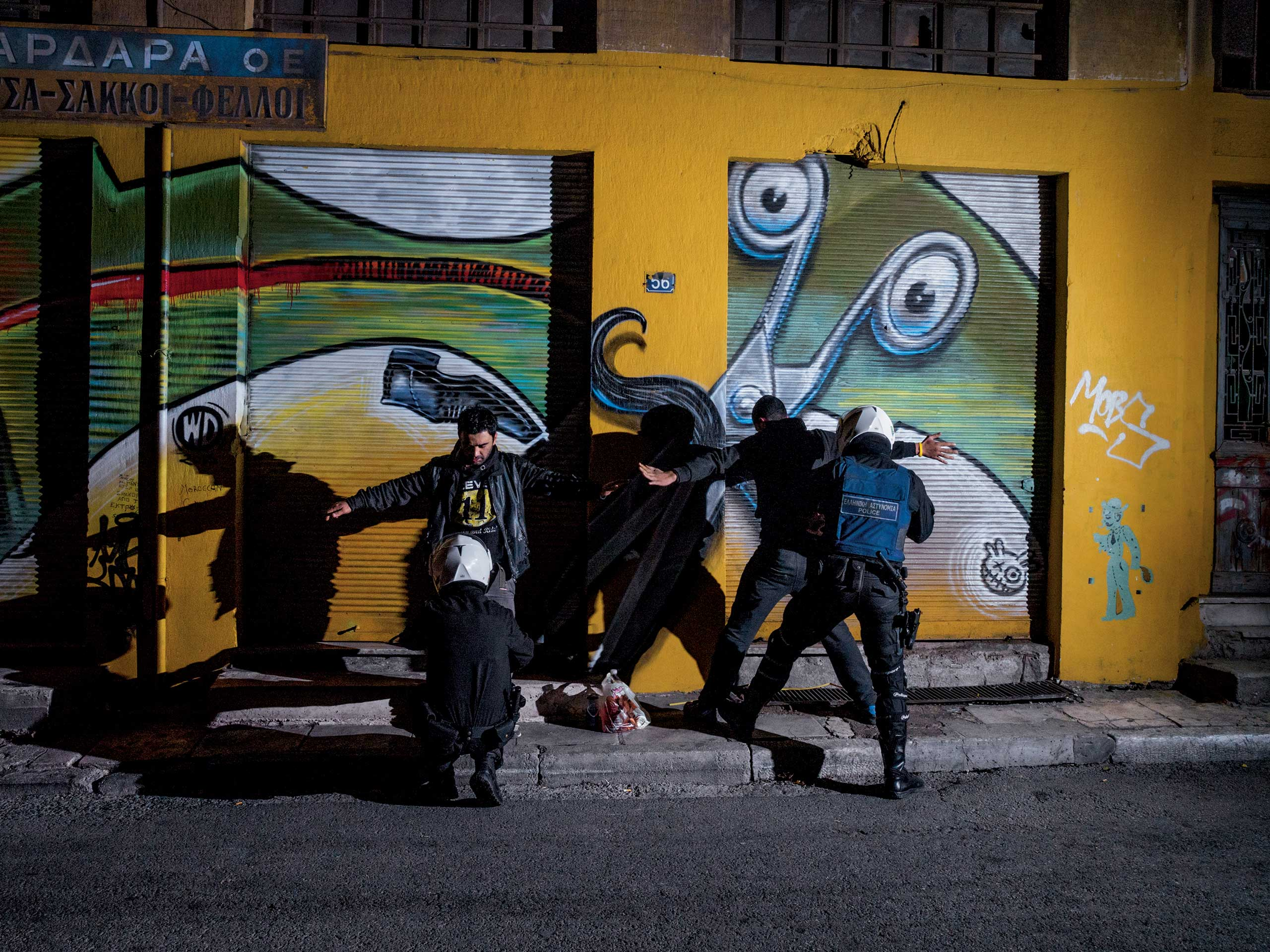 From the March issue of National Geographic magazine: Athens                               Police frisk young men on Aeschylus Street, near Omonia Square in Athens. Rates of drug use, prostitution, and HIV infection have risen in the area since the crisis began.