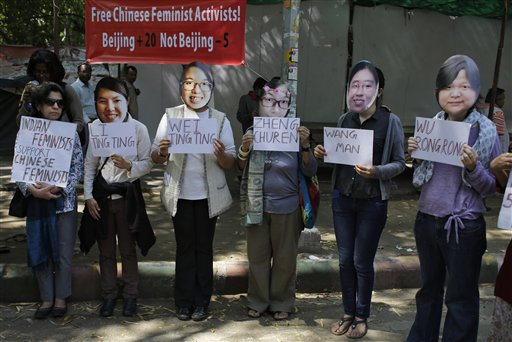 Indian women's rights activists wearing masks of five women's rights activists formally detained in China after Women's Day crackdown, hold placards with their names, to express their solidarity and demand their immediate release, in New Delhi, India, Wednesday, March 18, 2015
