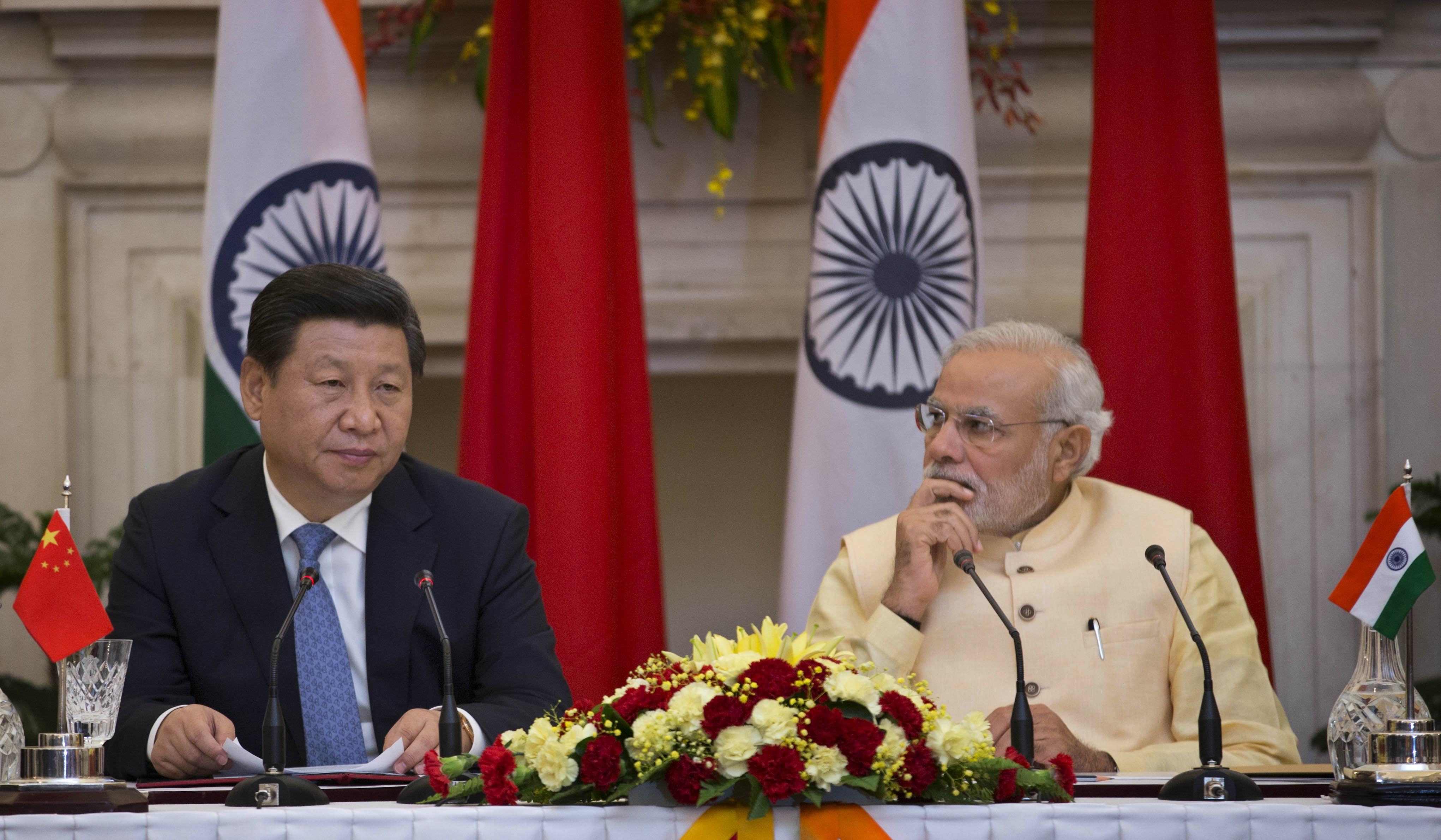 Chinese President Xi Jinping (L) makes a statement before the media as Indian Prime Minister Narendra Modi (R) watches after signing agreements in New Delhi, India on Sept. 18, 2014.