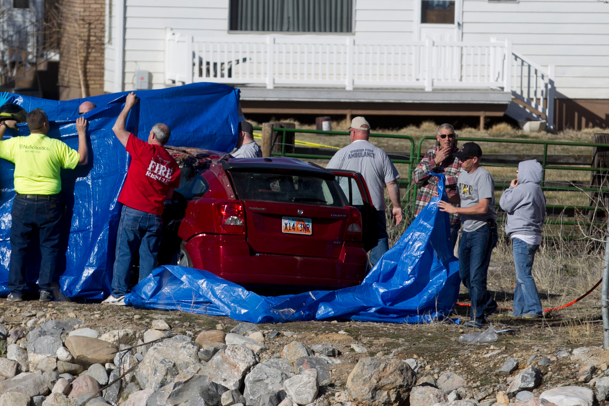 In this March 7, 2015 photo, officials respond to a report of a car crash in a river in Spanish Fork, Utah