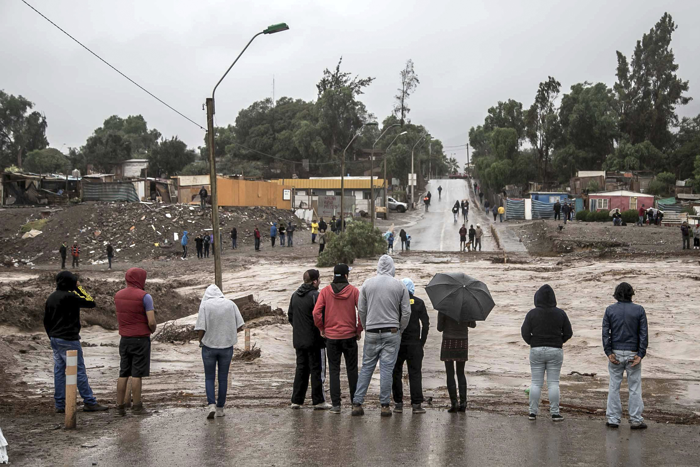 Residents watch the rising flood waters of the Copiapo River, in Copiapo, Chile, March 25, 2015