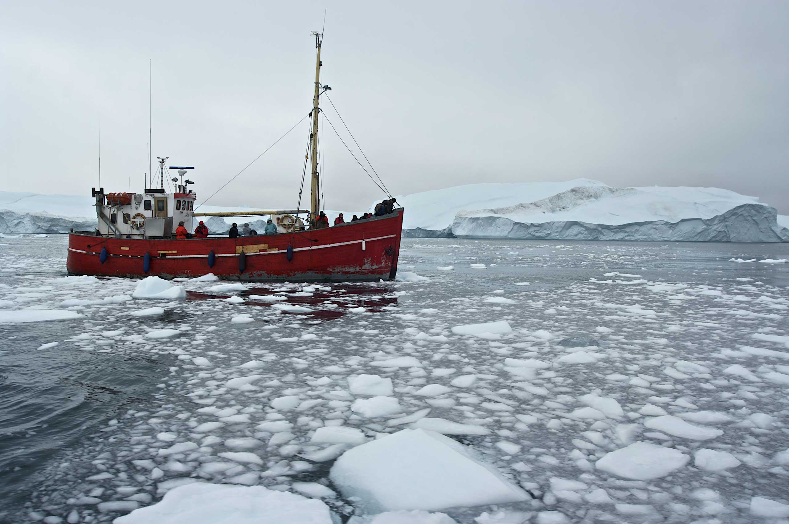Ship among the icebergs that have broken off the Sermeq Kujalleq ice sheet, Ilulissat, Qaasuitsup, Greenland.
