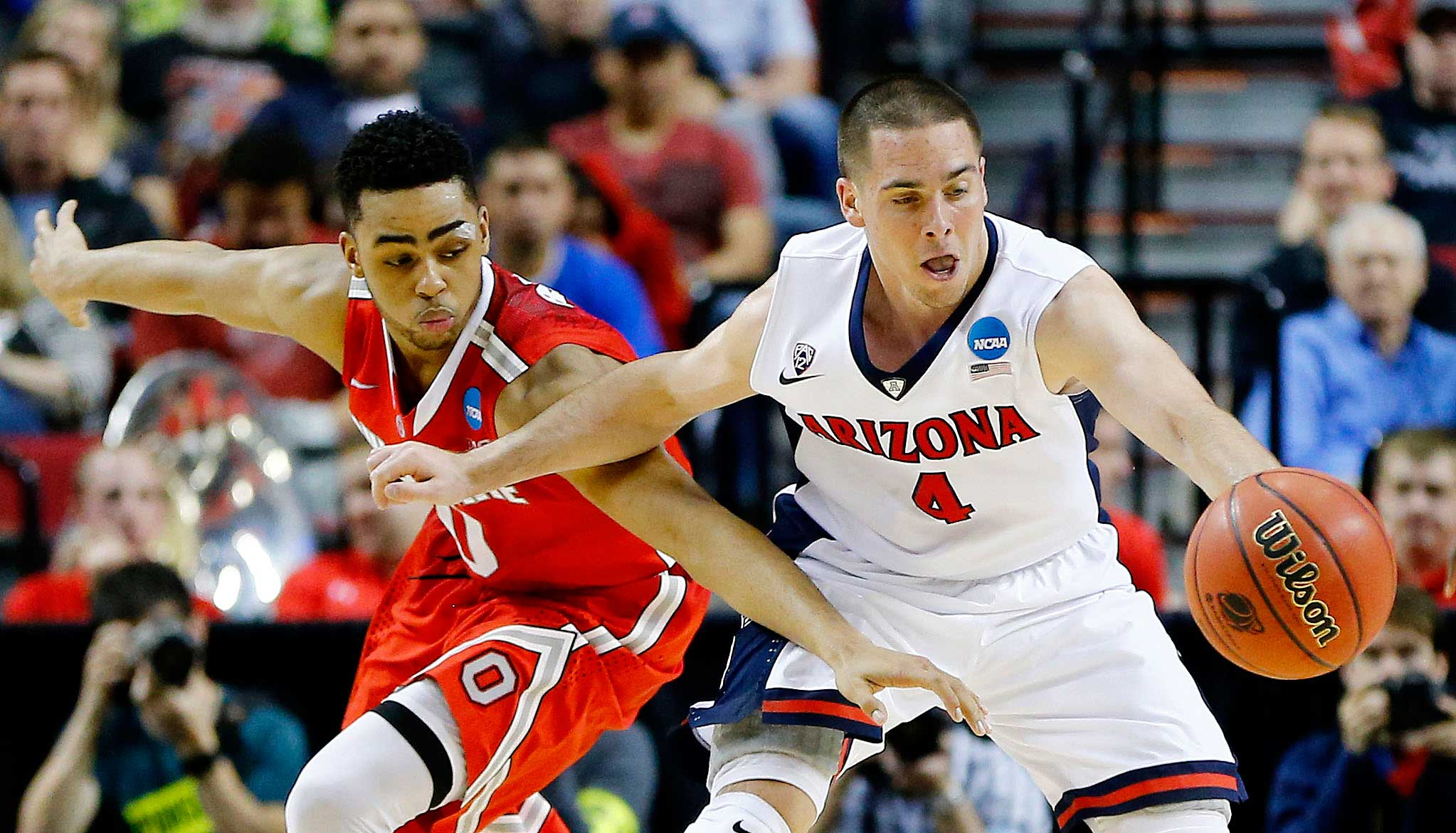 T.J. McConnell of the Arizona Wildcats and D'Angelo Russell of the Ohio State Buckeyes vie for a loose ball in the second half during the third round of the 2015 NCAA Men's Basketball Tournament at Moda Center in Portland, Ore. on March 21, 2015.