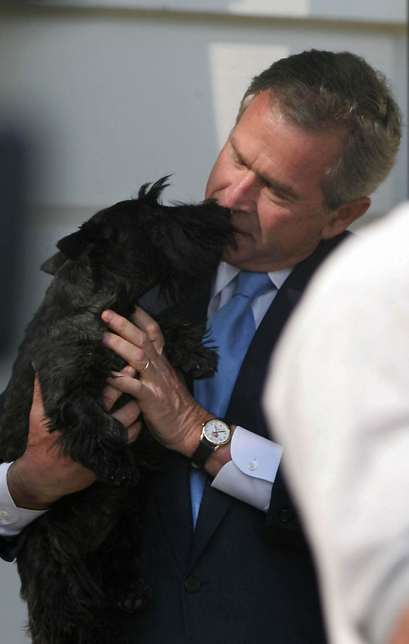 US President George W. Bush is greeted by one of his dogs after arriving from giving the commencement speech at Calvin College in Grand Rapids, Michigan, aboard Marine One on the south lawn of the White House in Washington on May, 21, 2005.