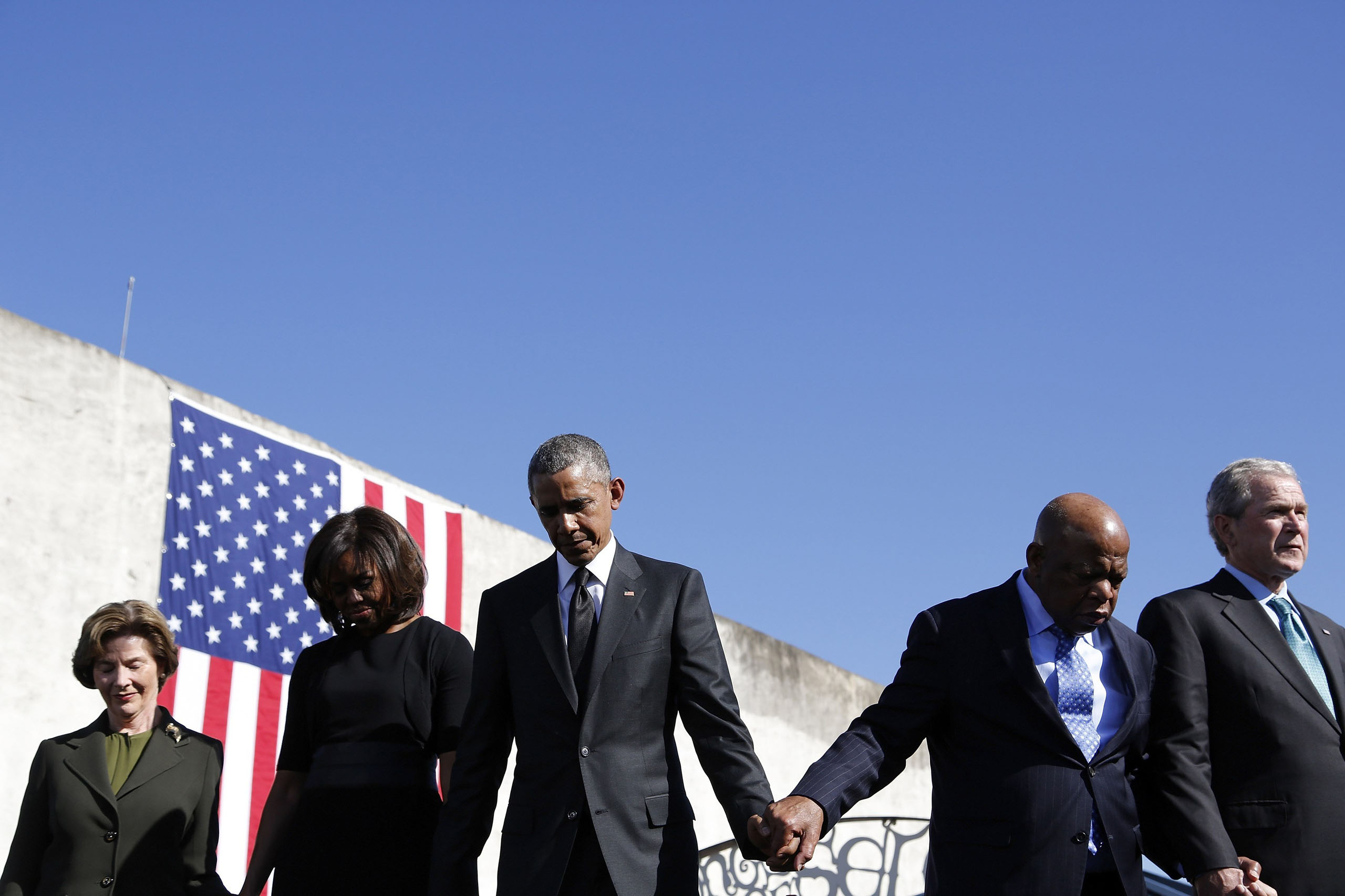 President Barack Obama and first lady Michelle Obama hold hands with former President George W. Bush and former first lady Laura Bush, and Rep. John Lewis during commemoration of the 50th anniversary of the 'Bloody Sunday' historical civil rights march at the Edmund Pettus Bridge in Selma, Ala. on March 7, 2015.
