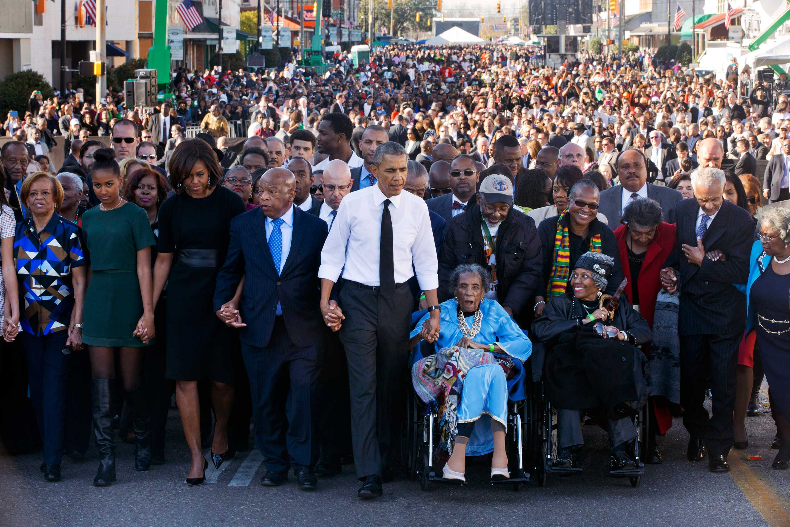 """President Barack Obama, center, walks as he holds hands with Amelia Boynton Robinson and Rep. John Lewis, who were beaten during 'Bloody Sunday,' as they and the first family walk across the Edmund Pettus Bridge on the 50th anniversary of """"Bloody Sunday"""" in Selma, Ala. on March 7, 2015."""