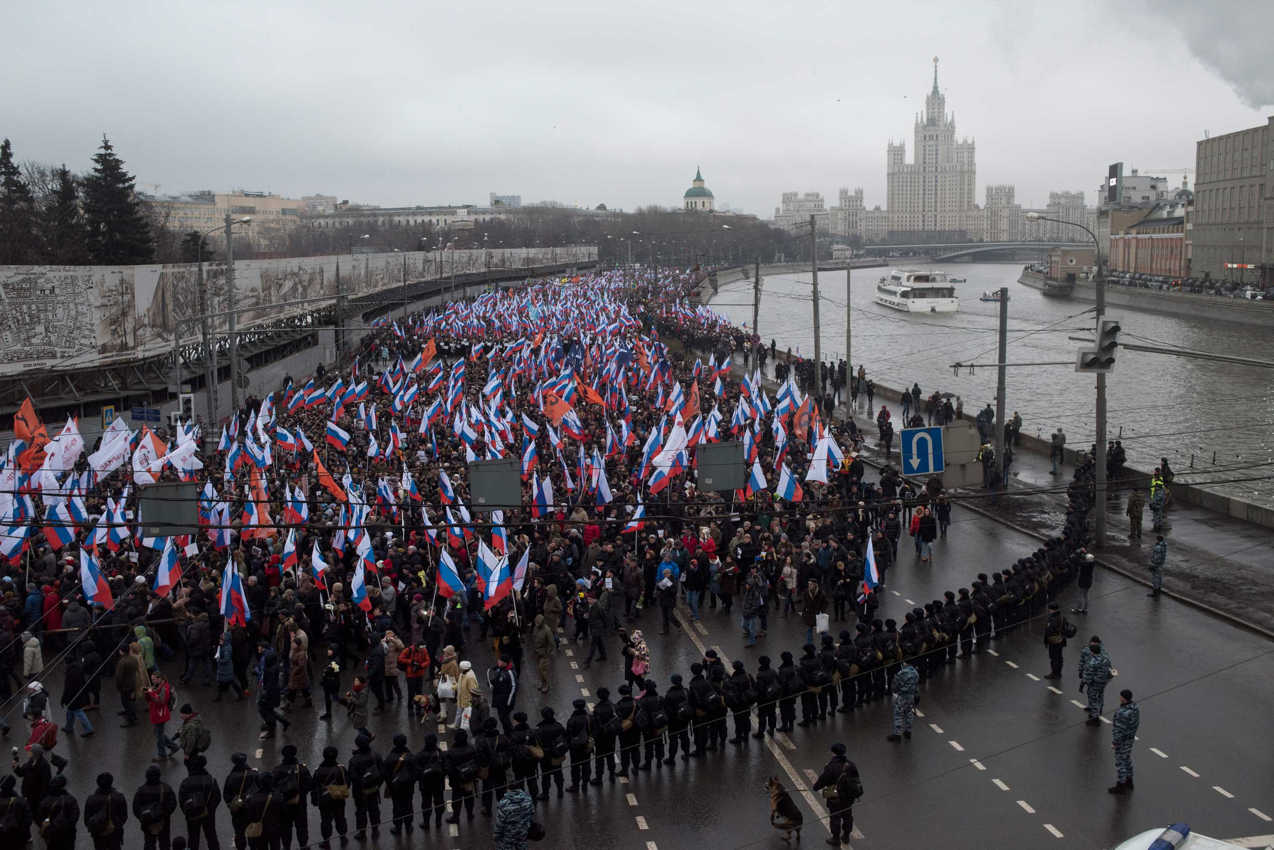 People carry Russian national flags as they march in memory of opposition leader Boris Nemtsov near the Kremlin in Moscow on March 1, 2015.
