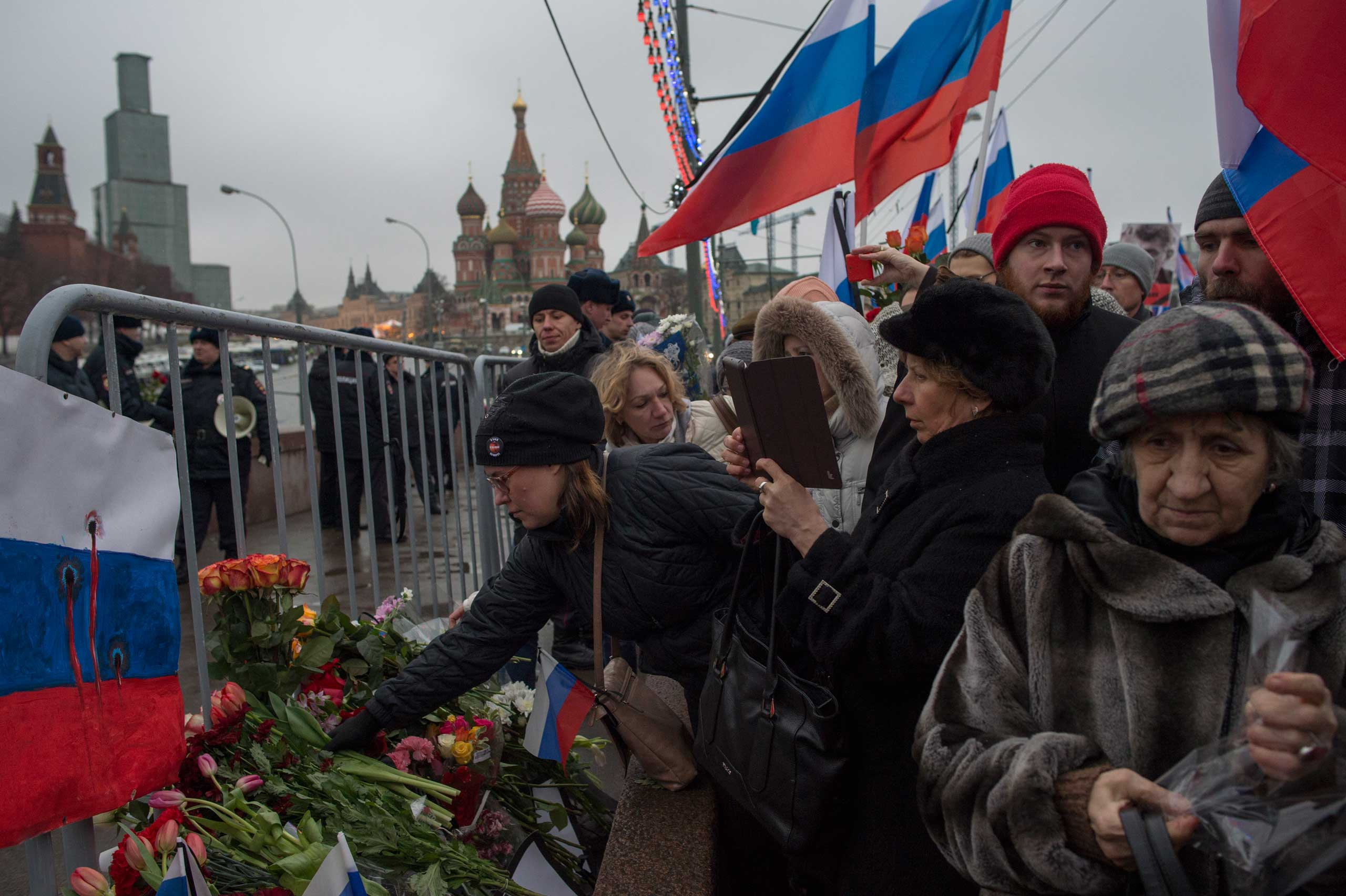 People lay flowers during the march in memory of opposition leader Boris Nemtsov near the Kremlin in Moscow on March 1, 2015.
