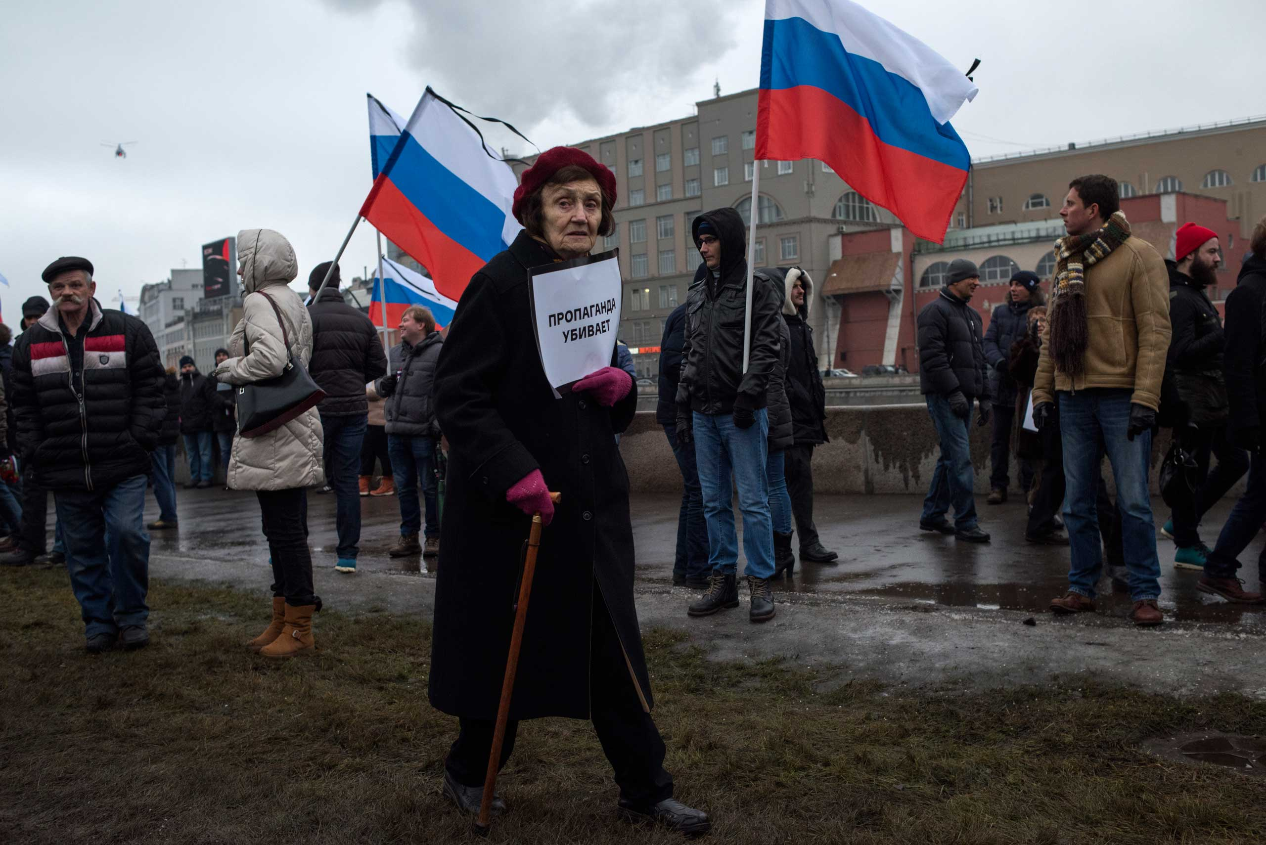 A woman holds a poster reading 'propaganda kills'  as people march in memory of opposition leader Boris Nemtsov near the Kremlin in Moscow on March 1, 2015.