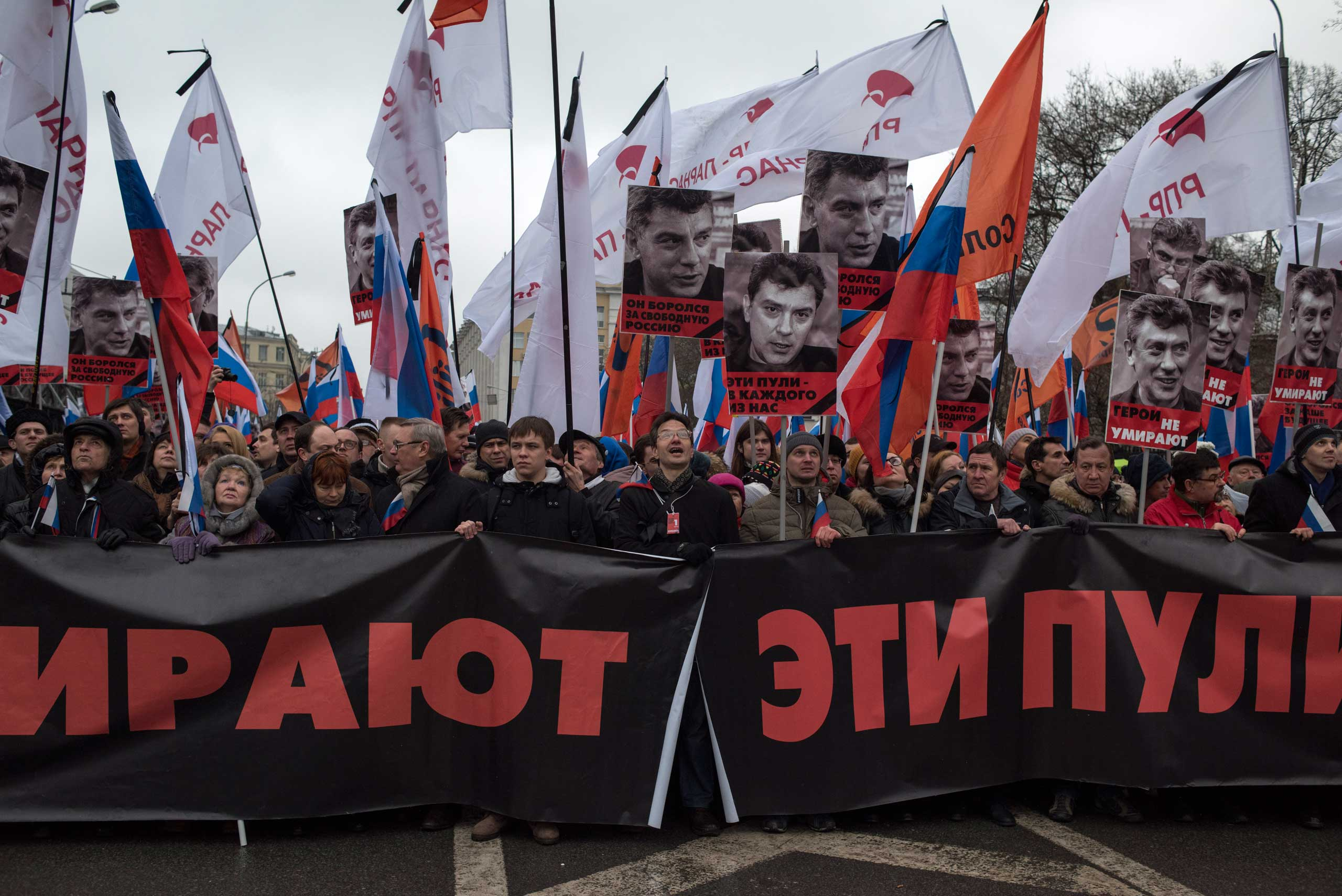 People march in memory of opposition leader Boris Nemtsov  with a  banner reading 'those bullets for everyone of us, heroes never die!' during the march in Moscow on March 1, 2015.