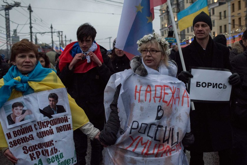 """Moscow, Russia, Sunday, March 1, 2015. People carry a huge banner reading 'those bullets for everyone of us, heroes never die!' as they march in memory of opposition leader Boris Nemtsov who was gunned down on Friday, Feb. 27, 2015 near the Kremlin.Thousands converged Sunday in central Moscow to mourn veteran liberal politician Boris Nemtsov, whose killing on the streets of the capital has shaken Russia's beleaguered opposition. They carried flowers, portraits and white signs that said """"I am not afraid."""""""