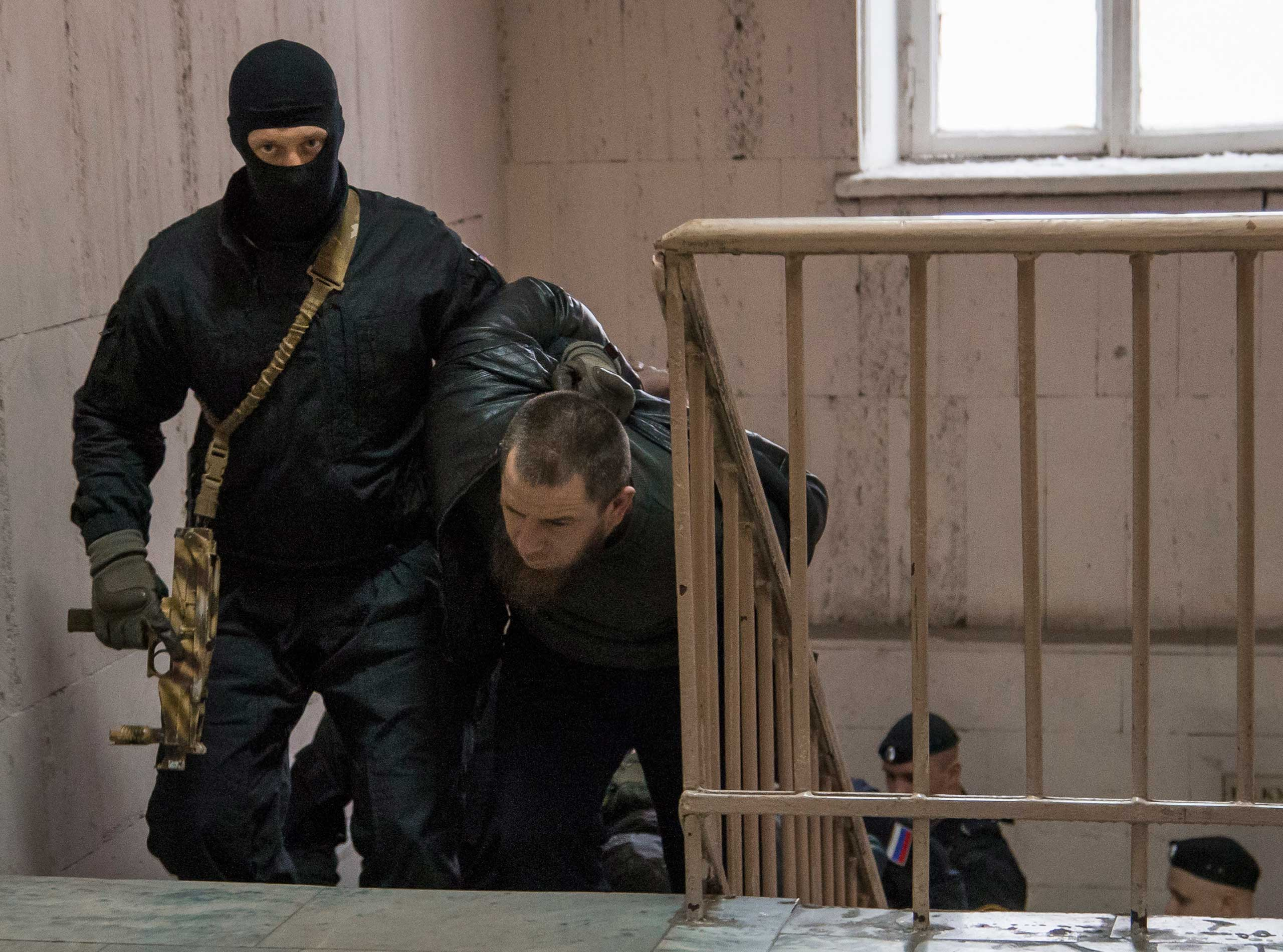 Police escort Tamerlan Eskerkhanov believed to be one of five suspects in the killing of Boris Nemtsov in a court room in Moscow on March 8, 2015