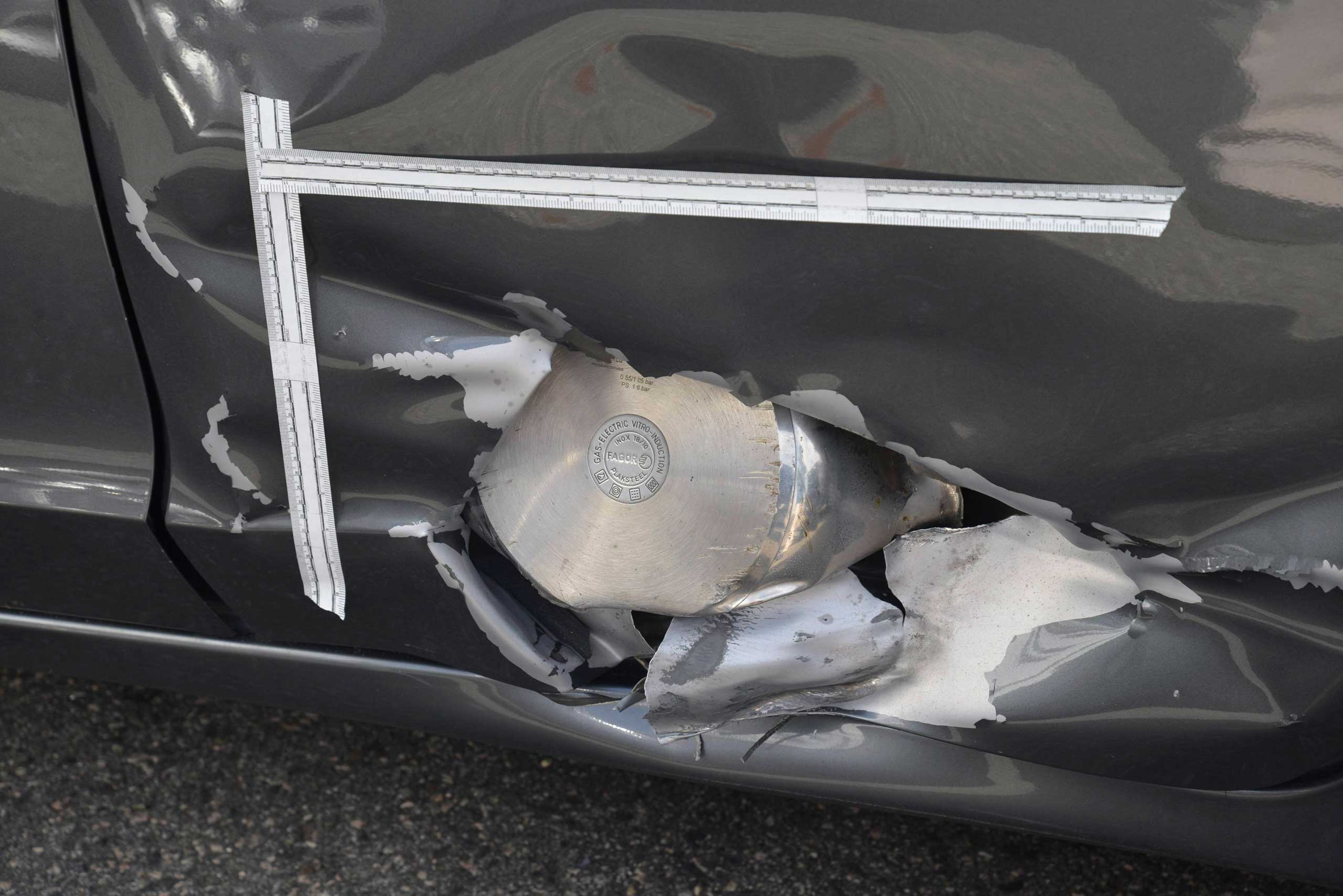 A large fragment of a homemade pressure-cooker bomb that accused Boston Marathon bomber Dzhokhar Tsarnaev is charged with throwing at police officers during a gunfight in Watertown, Mass. on April 19, 2015, is seen embedded in the side of a Honda Civic that was parked near the site of the disturbance.