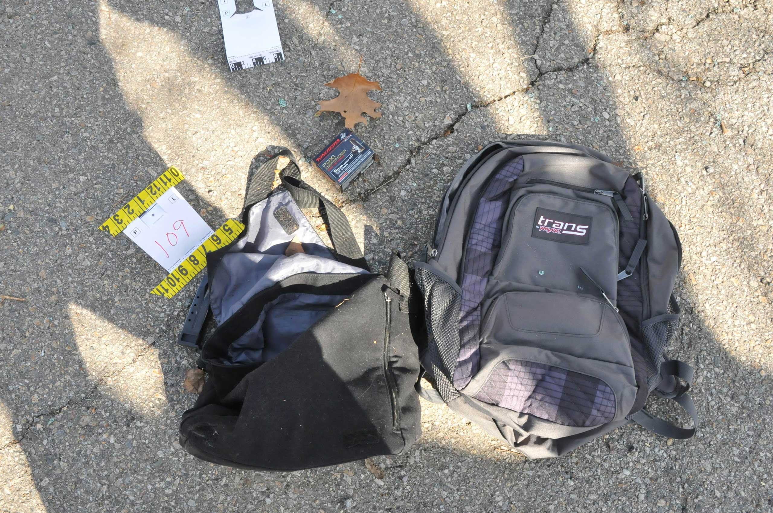 A 9mm Luger clip and bullet package sit next to a backpack and bag on a street where Tamerlan and Dzhokhar Tsarnaev engaged in a gunfight with police.