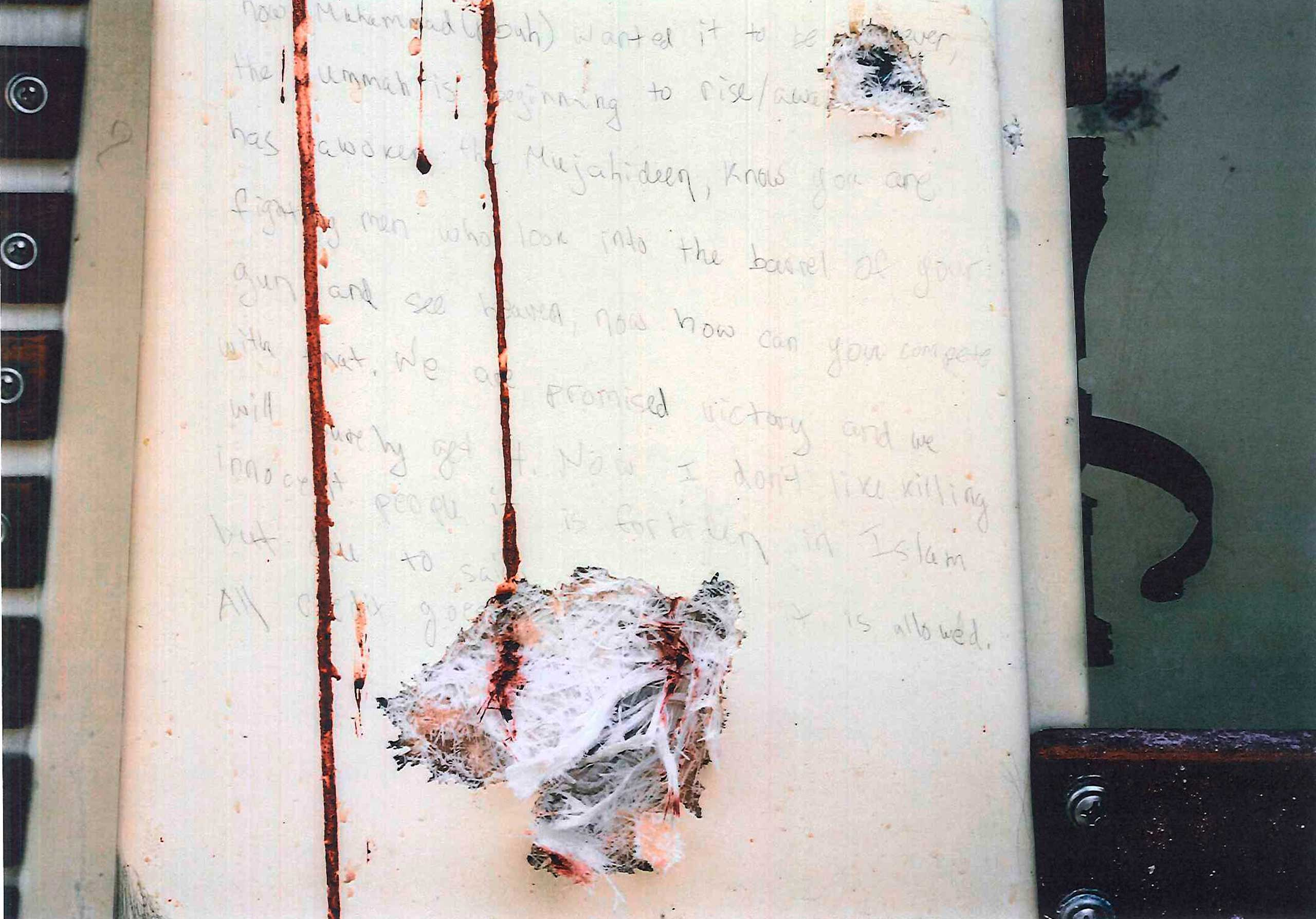 Prosecutors presented this image of a blood-stained, bullet-ridden message, allegedly written by Dzhokhar Tsarnaev on the inside of a boat, to jurors as evidence in Boston on March 10, 2015.