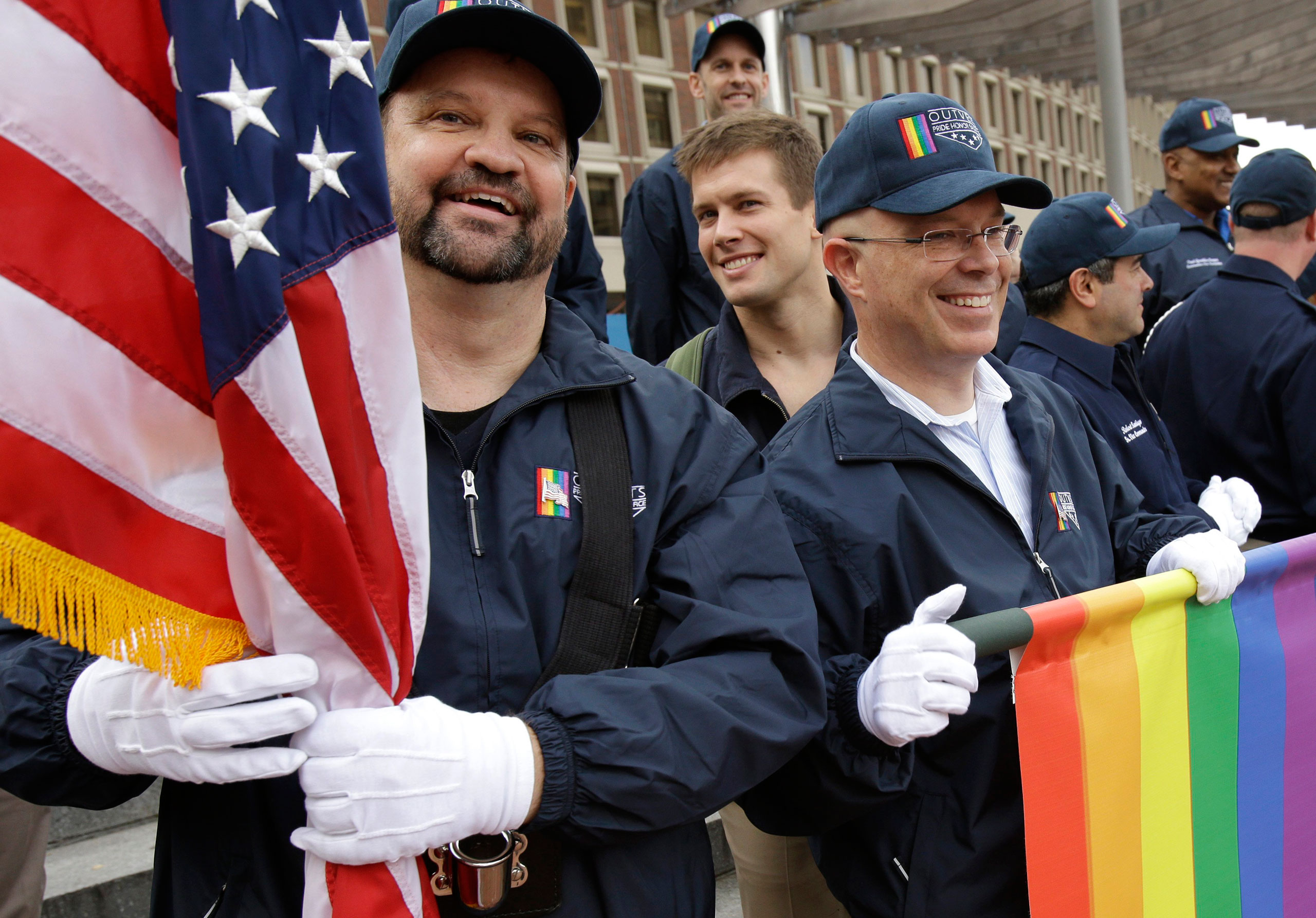 Retired U.S. Air Force Master Sgt. Eric Bullen, of Westborough, Mass., left, holds an American flag as U.S. Army veteran Ian Ryan, of Dennis, Mass., front right, rolls up an OutVets banner after marching with a group representing LGBT military veterans in a Veterans Day parade in Boston, Nov. 11, 2014. The organizers of Boston's annual St. Patrick's Day parade voted to allow the group of gay veterans along with a second group, Boston Pride, to march in this year's parade.