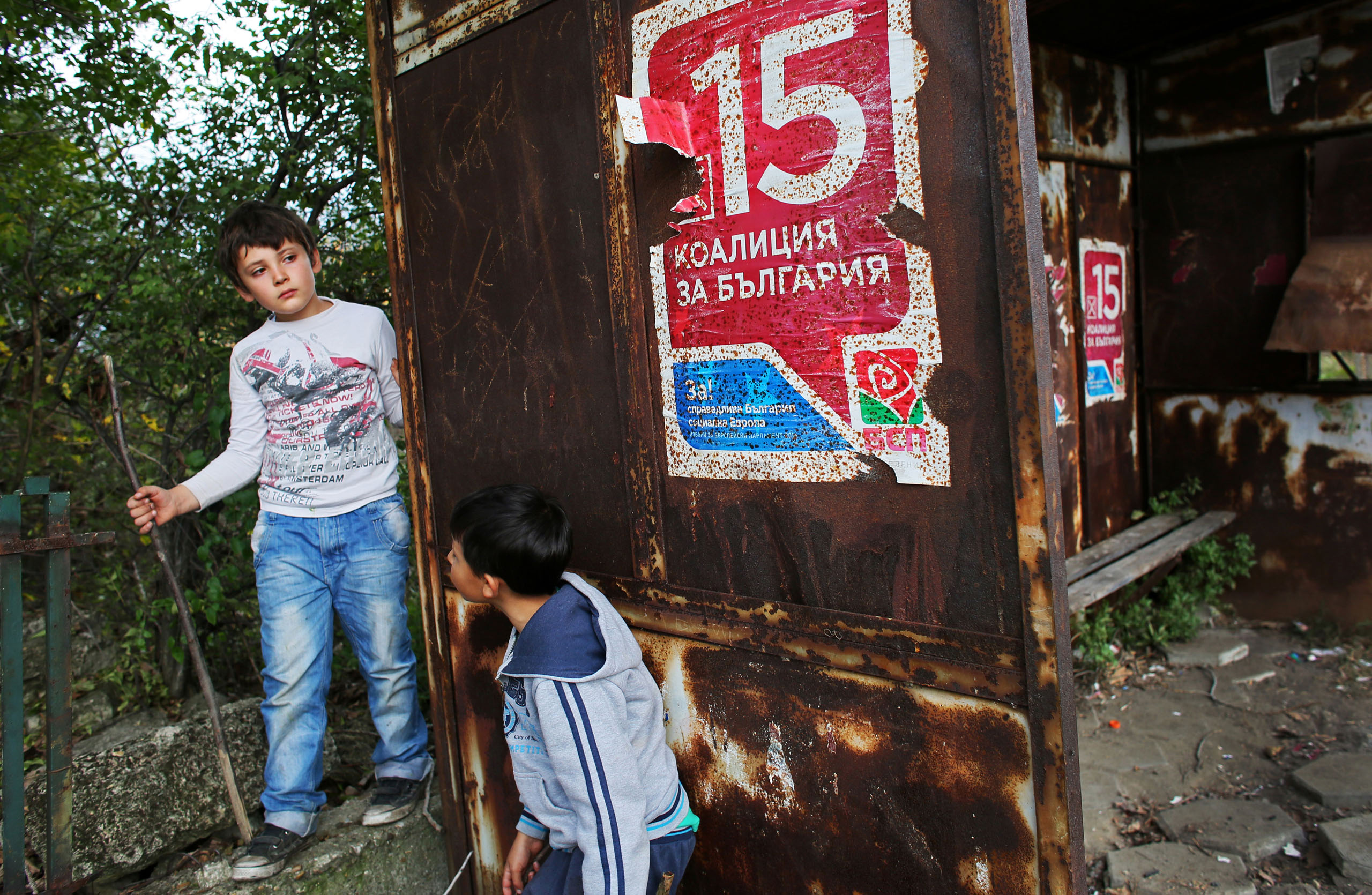 Young boys rest under a poster for Bulgaria's Socialist party at a decaying bus stop in Rabrovo, Northwest Bulgaria, Oct. 17, 2014.