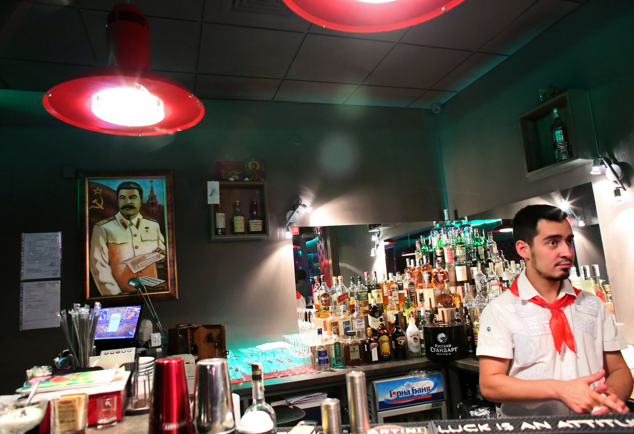Kristiyan Stamatov serves drinks in front of a portrait of Joseph Stalin, at SSSR, a USSR nostalgia restaurant and bar in Sofia, Oct. 4, 2014.