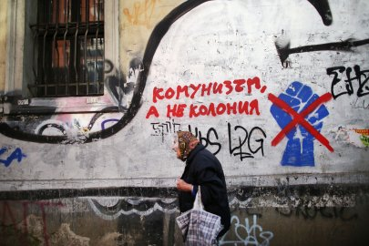 A woman walks by communist graffiti in Bulgaria's capital Sofia, on October 4th, 2014. This photo is from a project that aims to gauge the state and effect of democracy in the former Soviet satellite nation Bulgaria, two and a half decades after the fall of the Berlin Wall. The story of democracy in Bulgaria at age 25 is a cautionary tale about transplanting one-size-fits-all Western values to a nation still undergoing social and economic upheaval. Bulgaria is still one of the poorest, most corrupt nations in the European Union, its post-1989 hopes wilted by political instability, high crime rates and skyrocketing inflation. While Bulgarians can now freely vote and protest without much threat to their freedom, their new oppressor is corruption - which is at a 15 year high, across political and civil sectors alike. The ennui is so casually etched on the passerby's face that it becomes routine - one that fits in sadly well against a startling backdrop of rotting architecture, joblessness, and a vast population decline. Despite what democracy has changed in Bulgaria, the daily struggles of its populace remain largely untouched, trapped in a post-communist time capsule. This project was supported by a grant from The Pulitzer Center on Crisis Reporting. Photo by: Yana PaskovaCopyright © Yana Paskova 2014