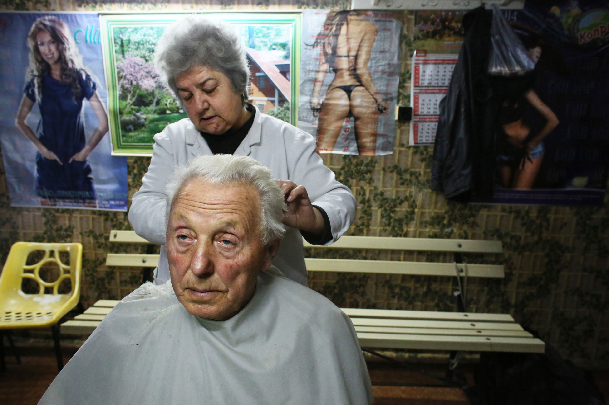 Hairdresser Pavlinka Paskova, 59, cuts the hair of Stanko Petrov Vulchev, 80, in Vidin, Oct. 30, 2014. Paskova says she has very few customers in this town of waning population:  There's little hope of prosperity for the young here - they've all emigrated.