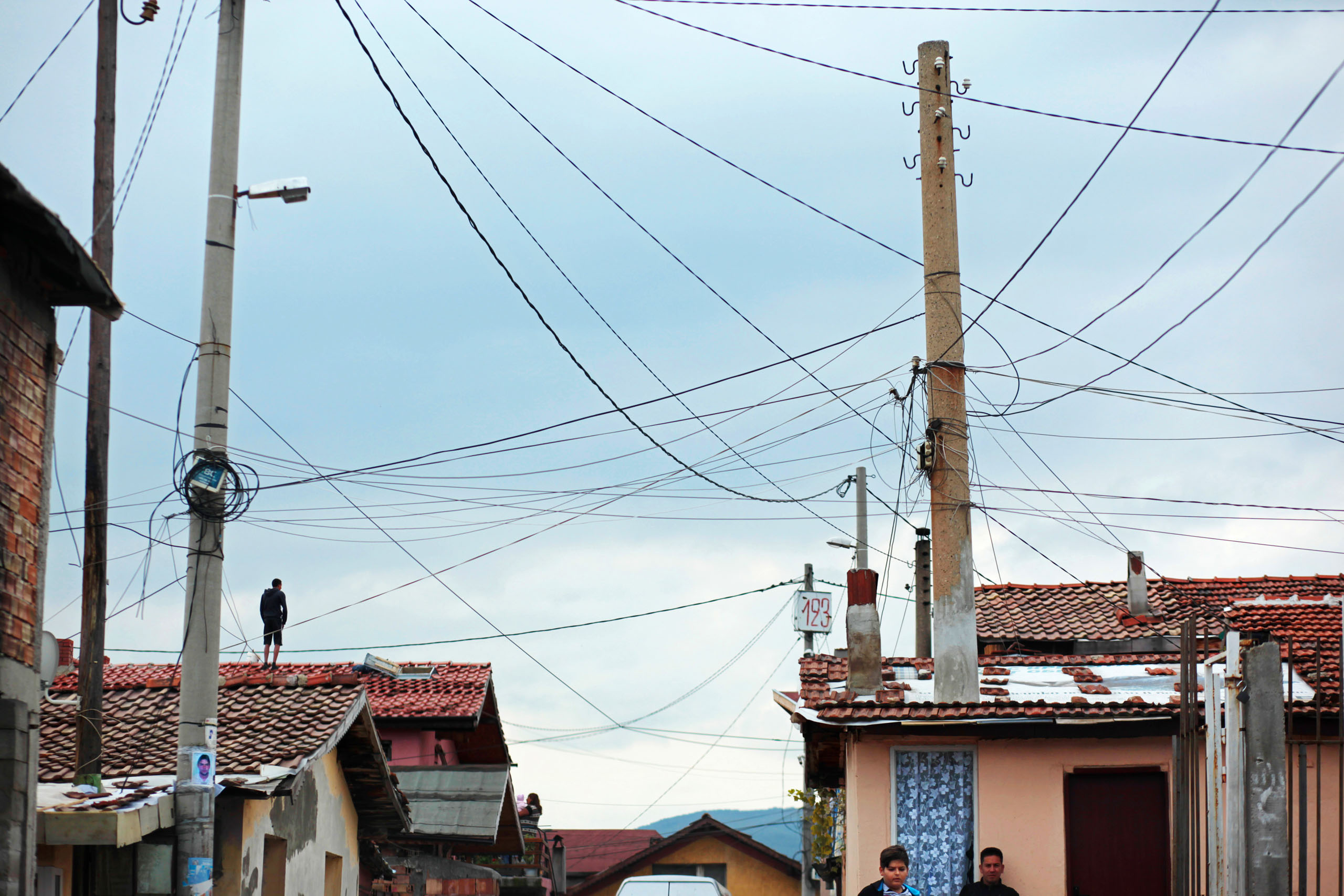 A man stands on a rooftop below a handmade electrical grid hanging over a Roma village, as people turn up to vote in October's Parliamentary elections in Sofia, Bulgaria, Oct. 5, 2014.