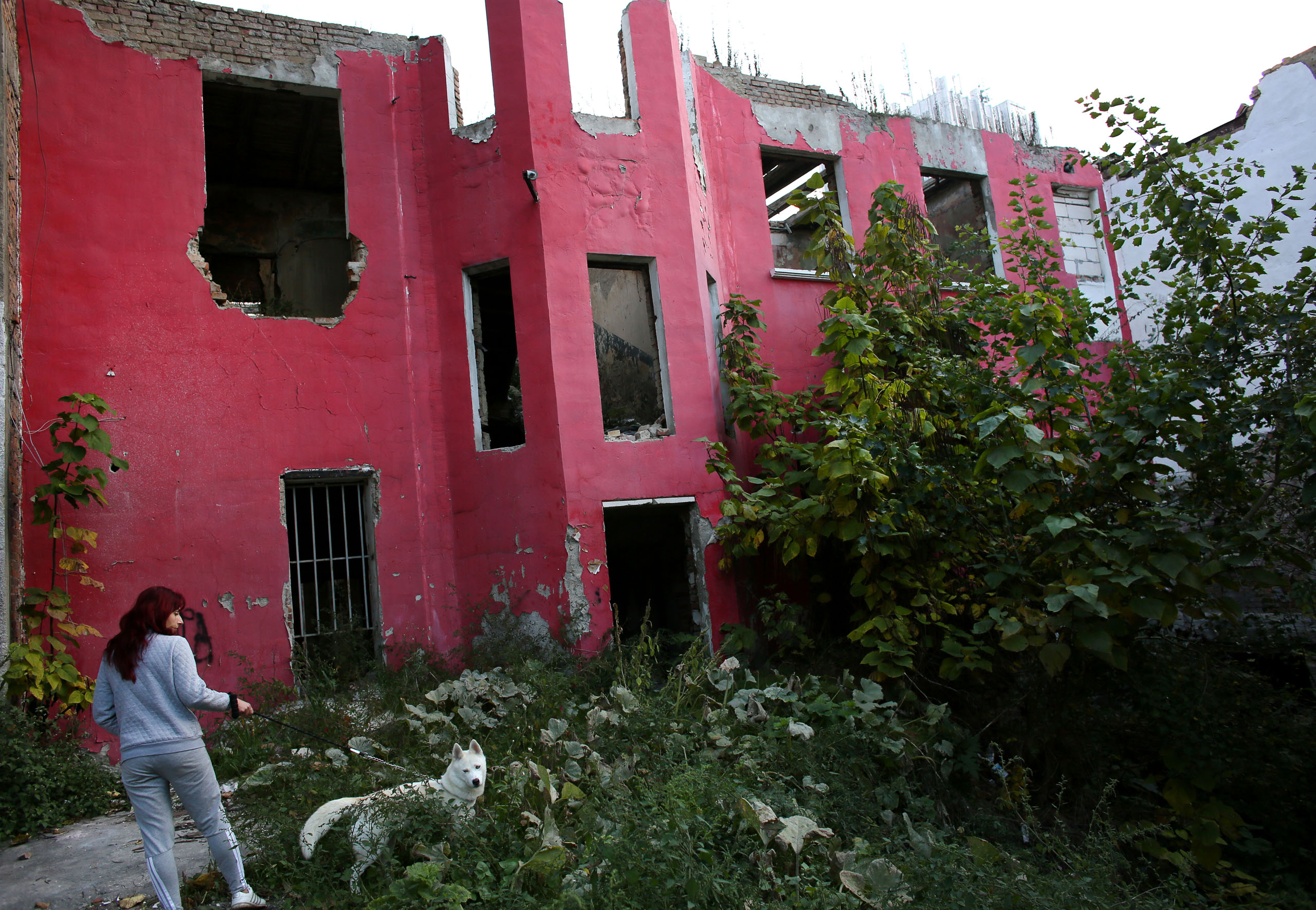 A woman walks her dog by an abandoned building in Vidin, a town in Bulgaria, Oct. 22, 2014.