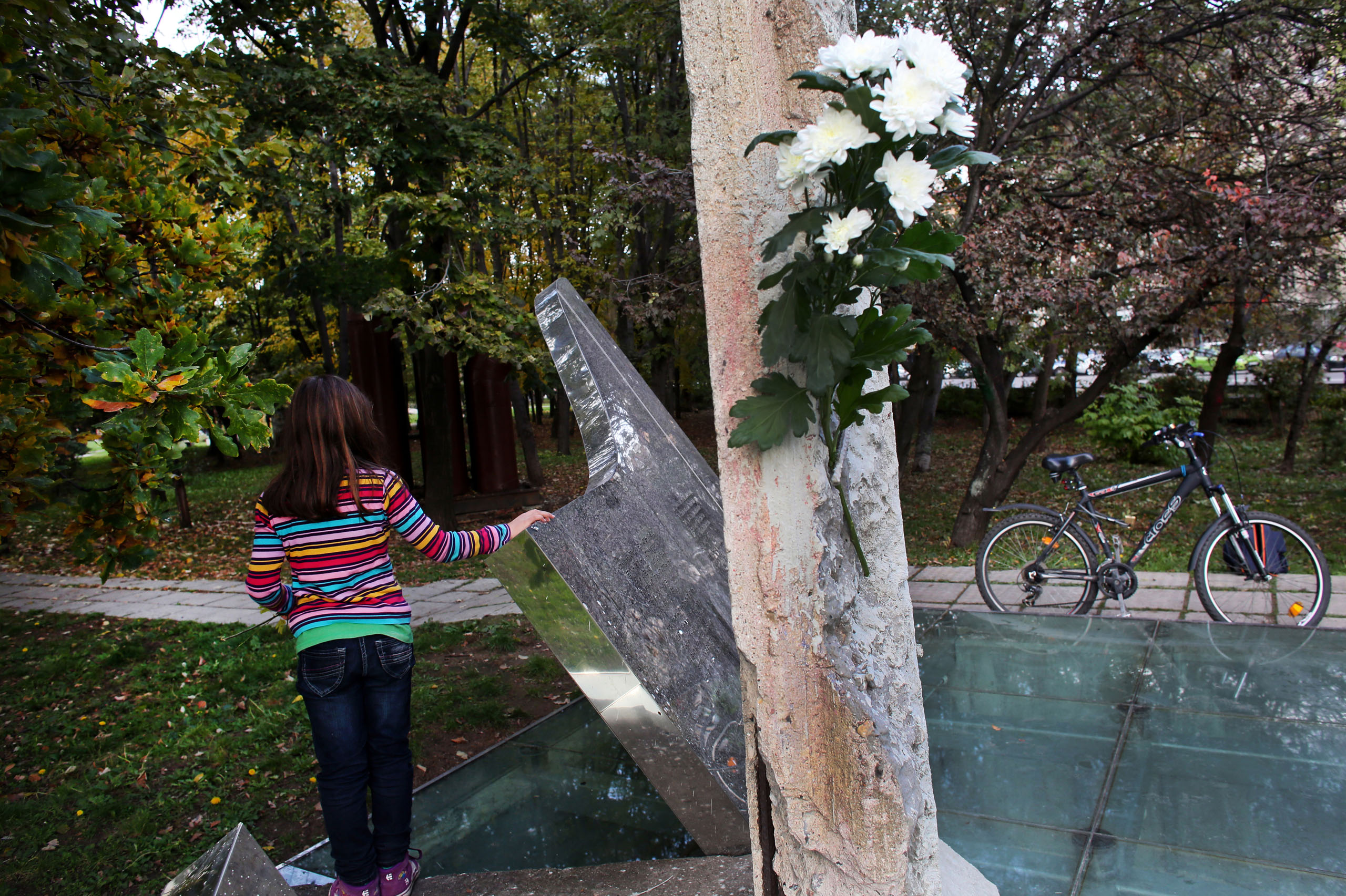 A child leans on a piece of the Berlin Wall on Nov. 9, 2014, on the 25th anniversary of the fall of the wall. This piece was gifted to Bulgaria's capital Sofia in 2006.