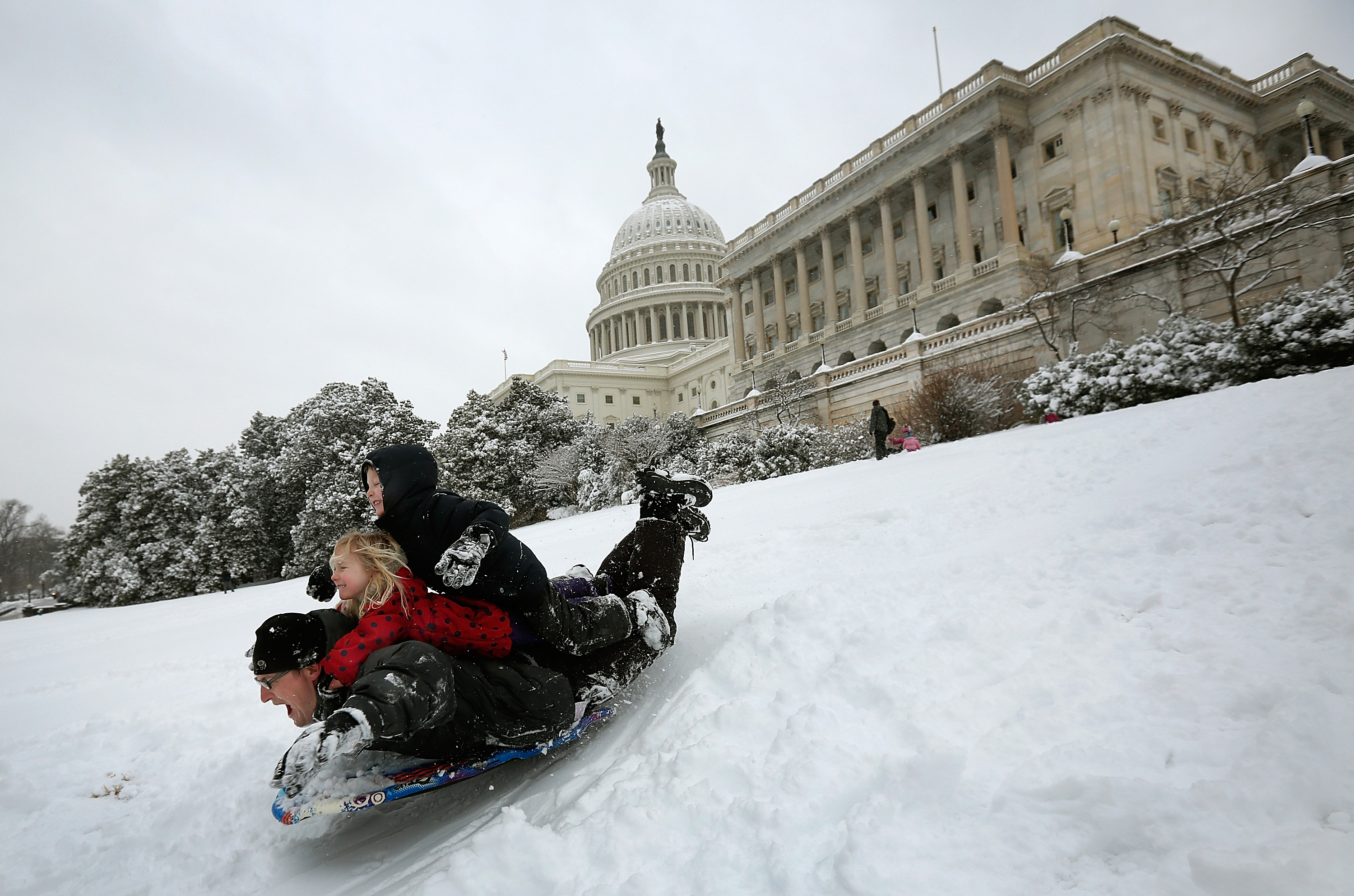 Jon Ward sleds with his daughter Gwen and son Jethro on the west lawn of the U.S. Capitol on March 17, 2014 in Washington D.C.