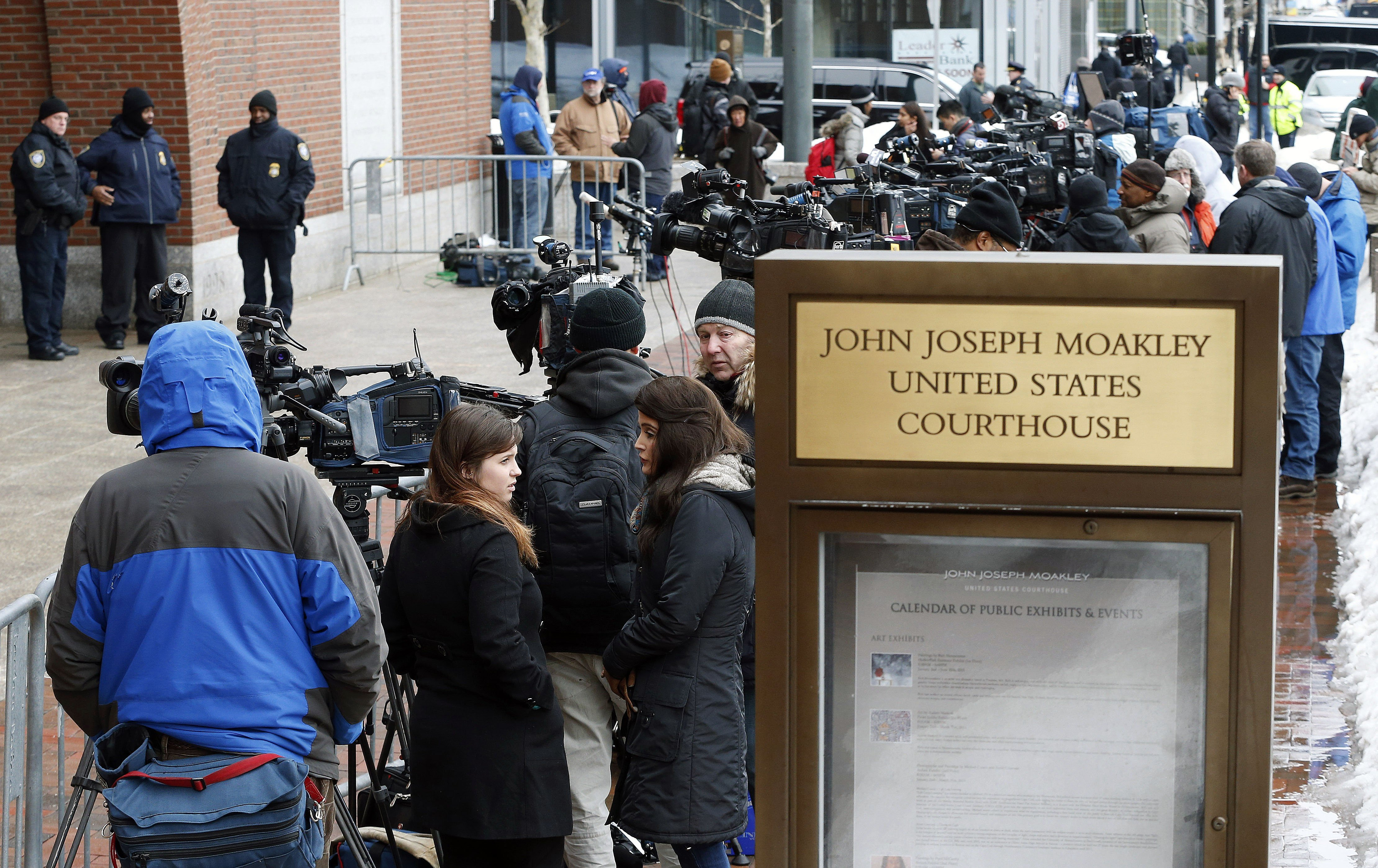 Members of the media wait outside federal court on March 4, 2015 in Boston.