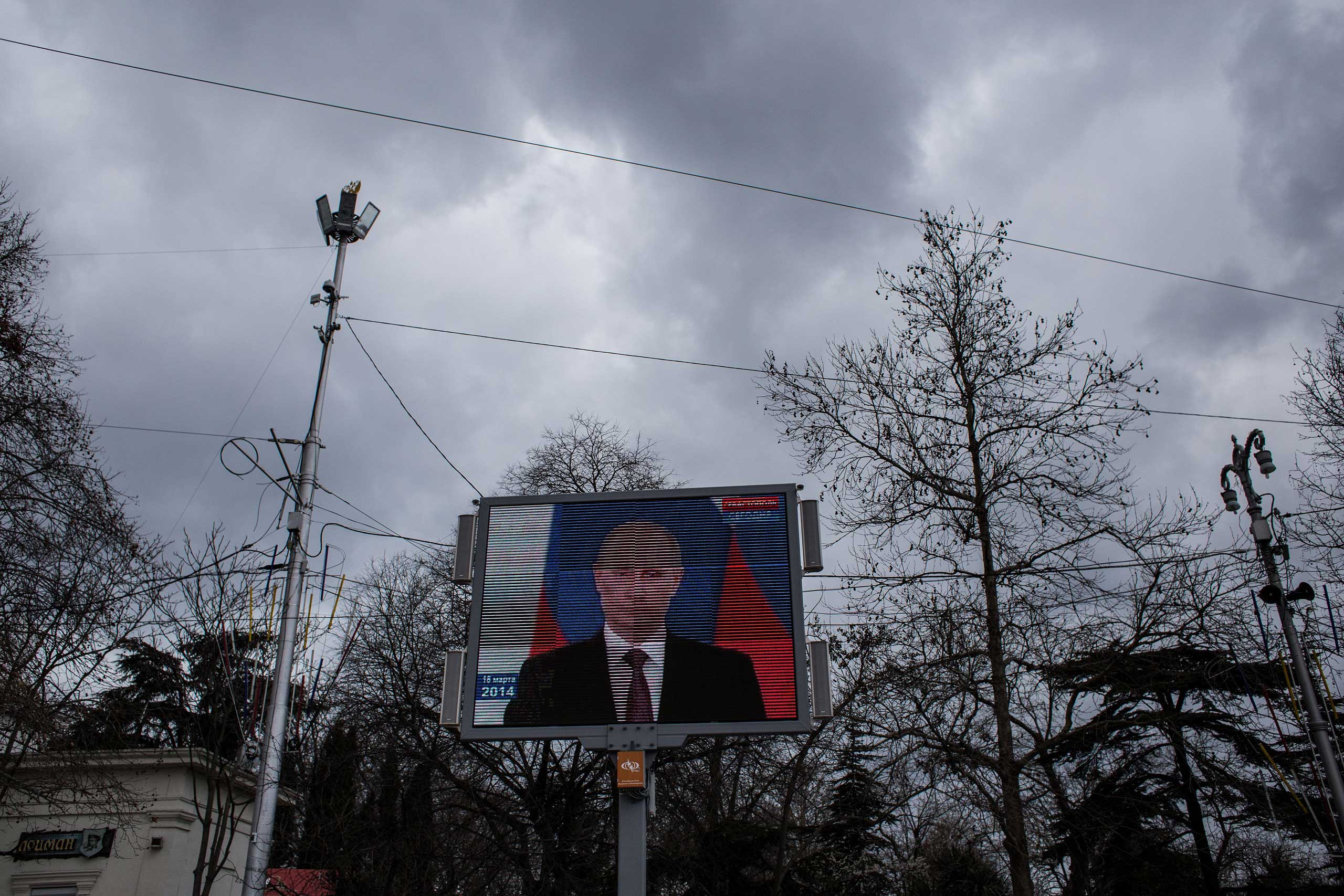 A video of Russian President Vladimir Putin signing the decree is shown on the first anniversary of the annexation, March 18, 2015 in Sevastopol.