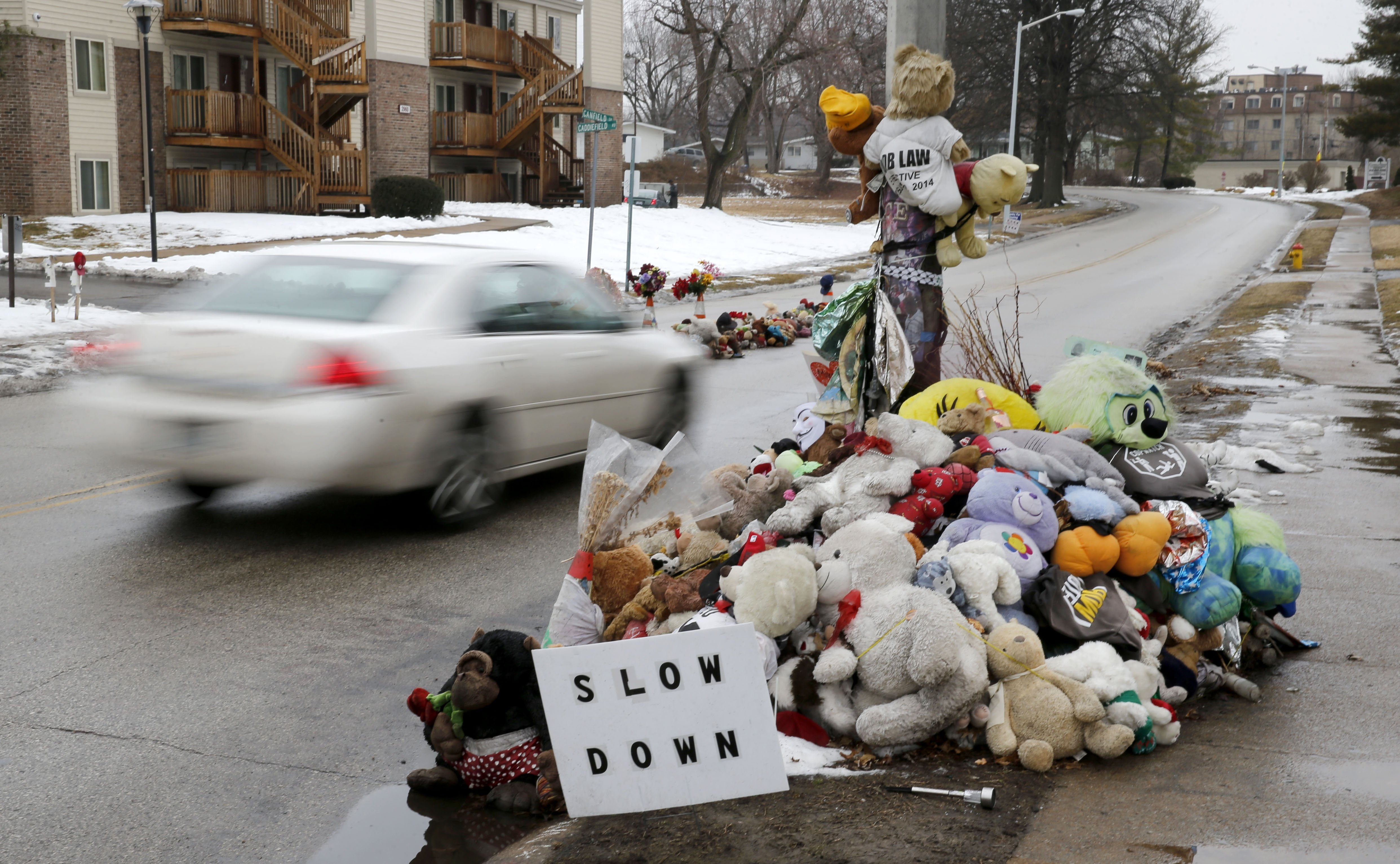 A car passes a memorial for Michael Brown, who was shot and killed by Ferguson, Mo., Police Officer Darren Wilson last summer, March 3, 2015, in Ferguson, Mo.