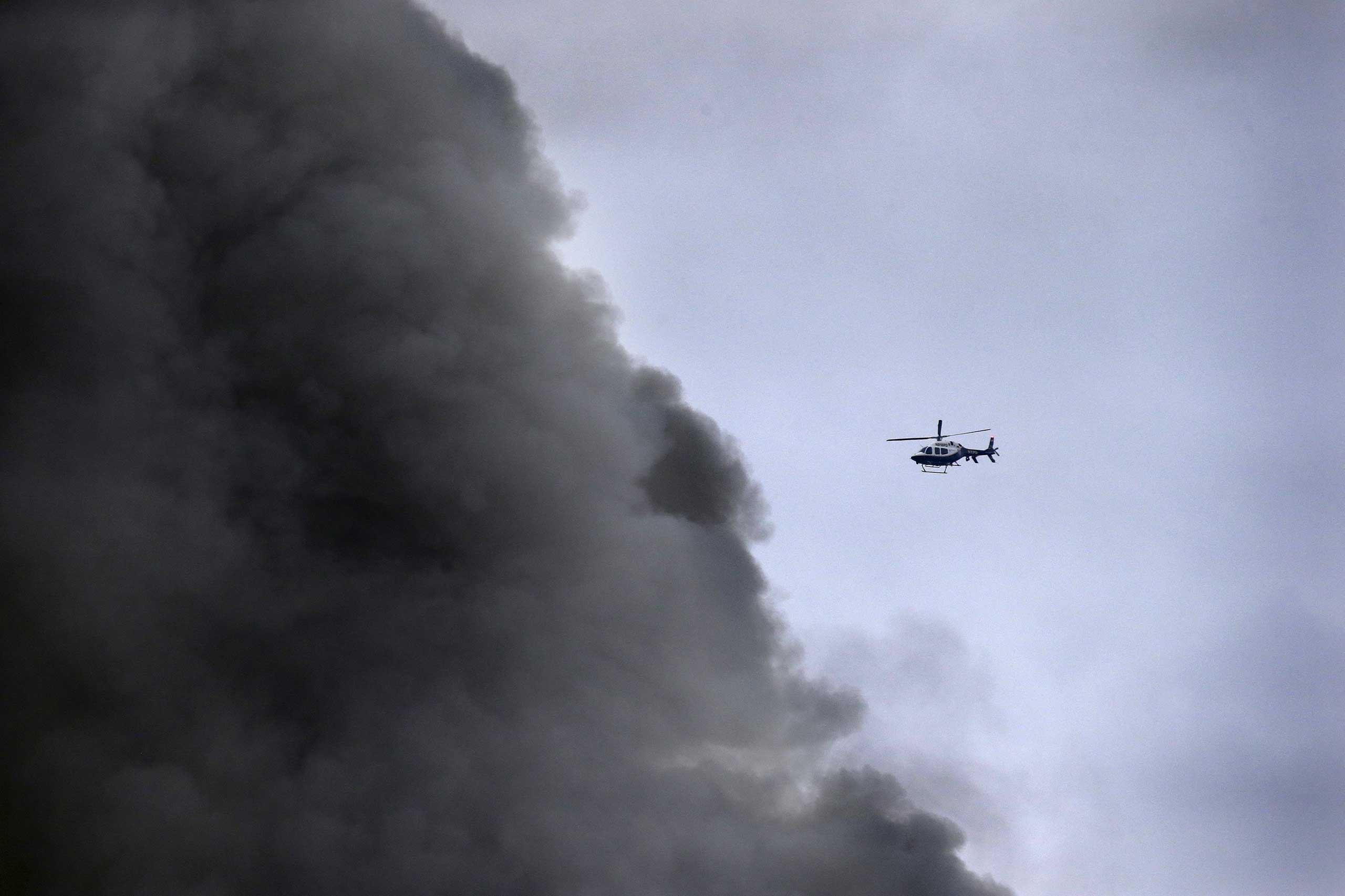 A New York City Police helicopter flies near billowing smoke above the site of a residential apartment building collapse and fire in the East Village neighborhood of New York City on March 26, 2015.