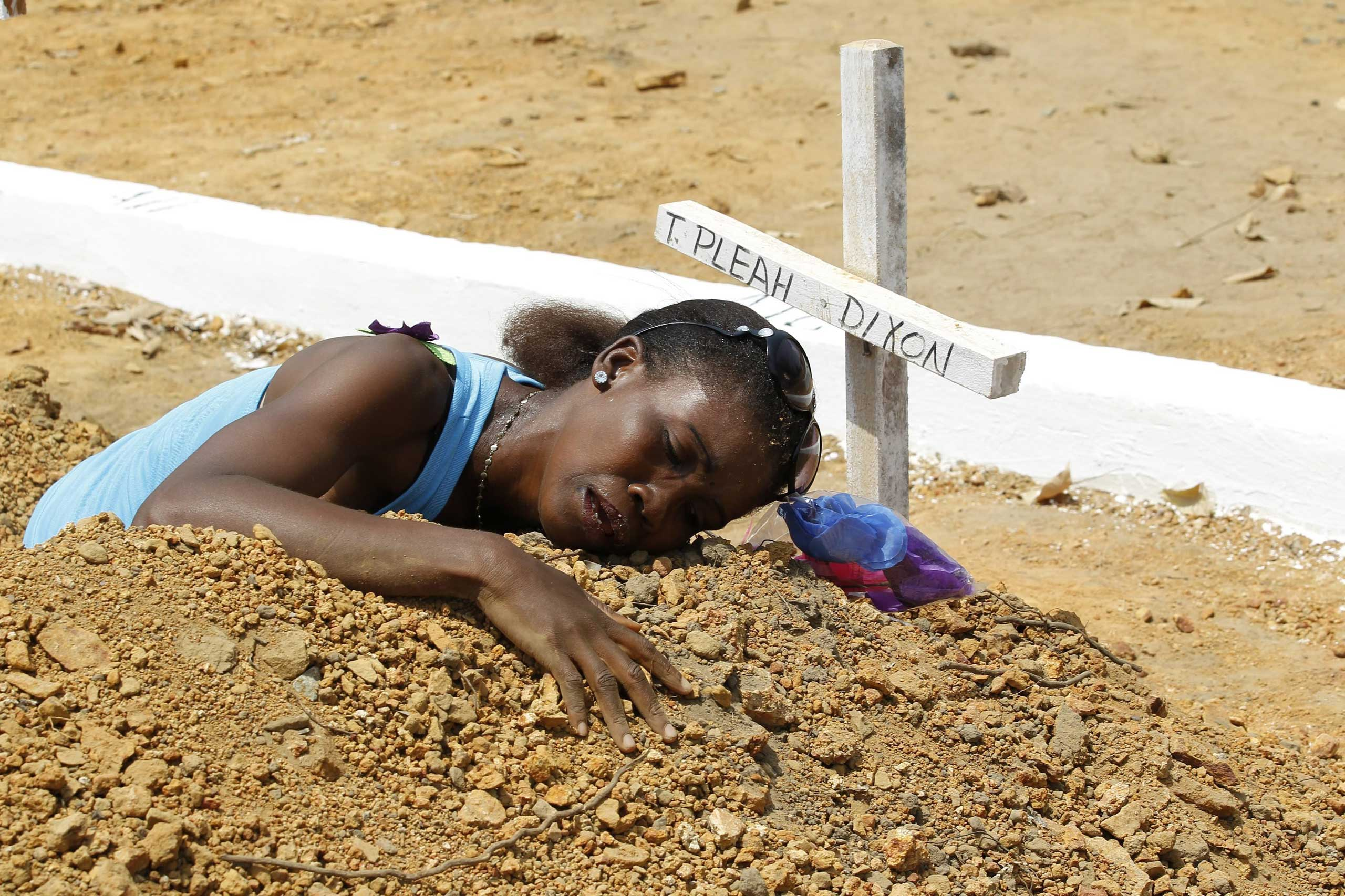 A woman mourns at the grave of her late brother at the National Cemetry on Disco Hill, Margibi County, Liberia, on March 11, 2015